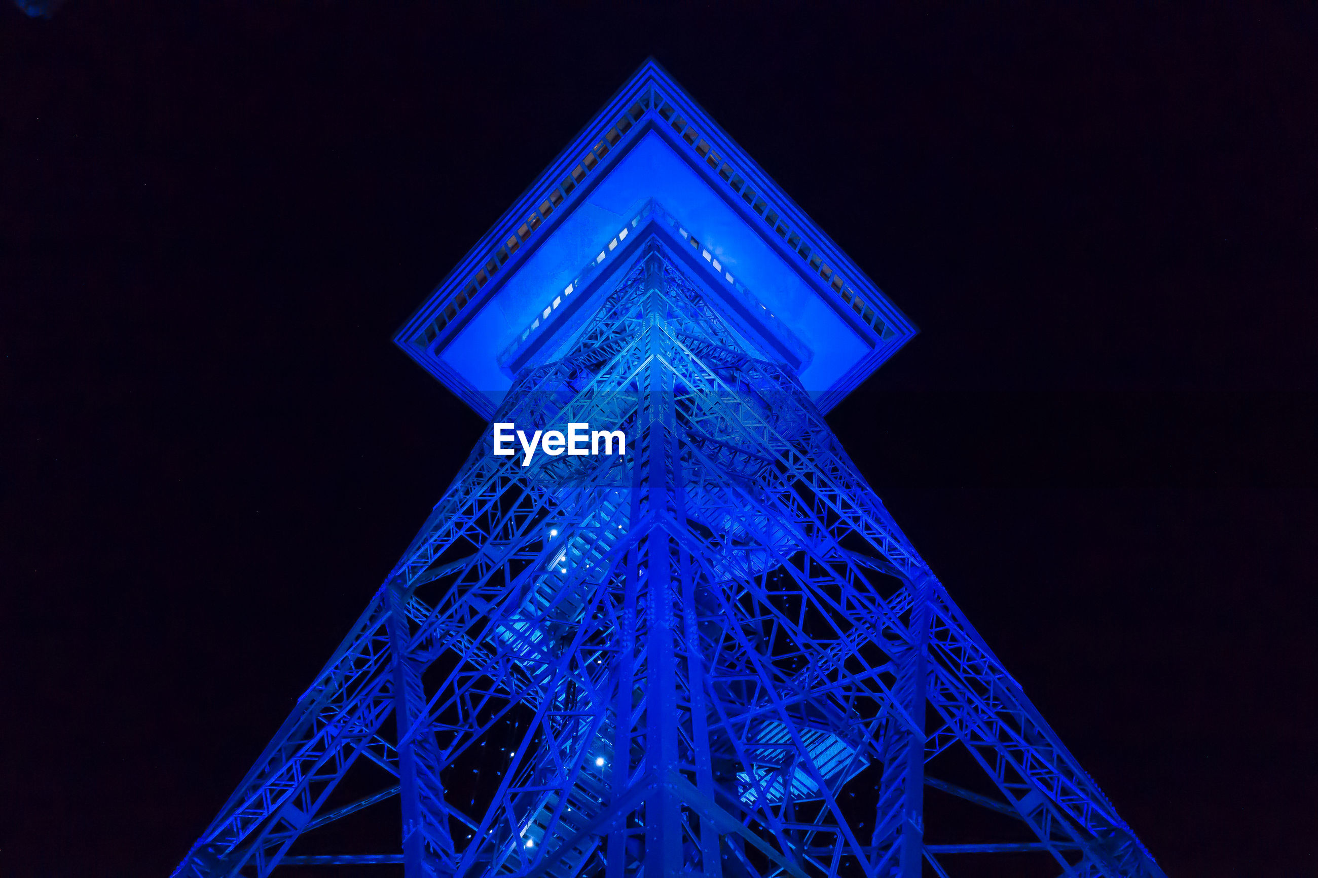 Directly below shot of illuminated tower against clear sky at night