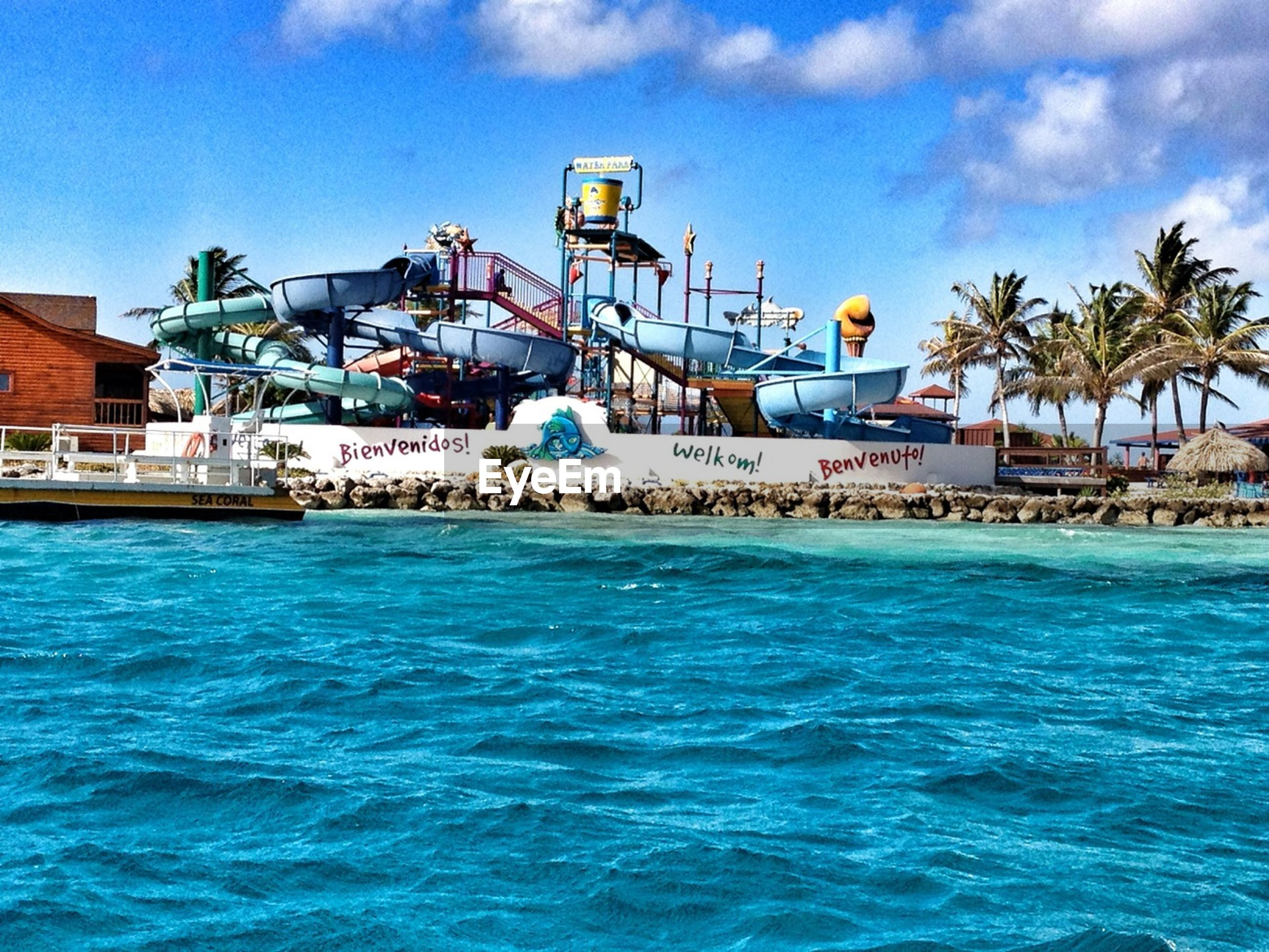 water, blue, sky, built structure, waterfront, architecture, building exterior, sea, nautical vessel, swimming pool, cloud, cloud - sky, moored, boat, house, transportation, palm tree, mode of transport, tree, turquoise colored