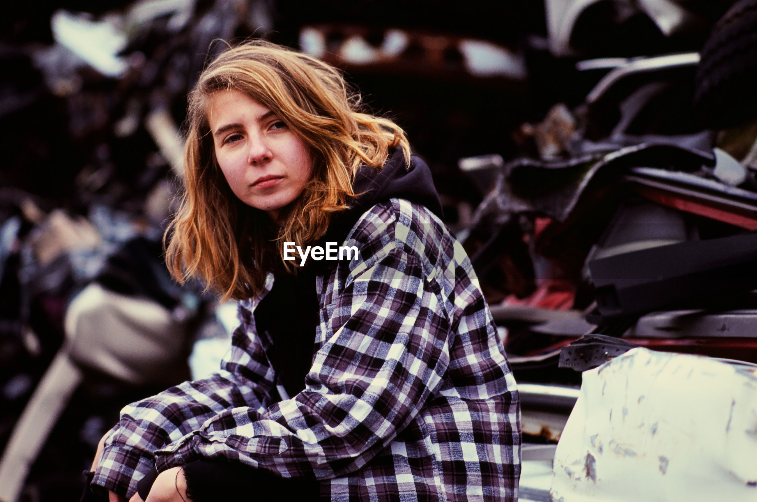 Young woman sitting in auto salvage yard
