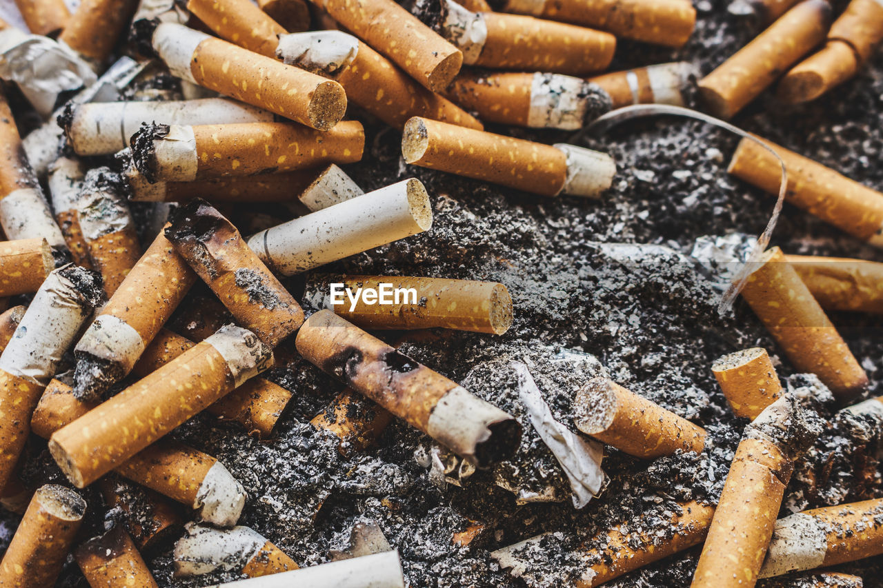 smoking issues, cigarette butt, cigarette, bad habit, burnt, sign, ash, warning sign, risk, tobacco product, communication, ashtray, large group of objects, social issues, no people, close-up, still life, abundance, excess