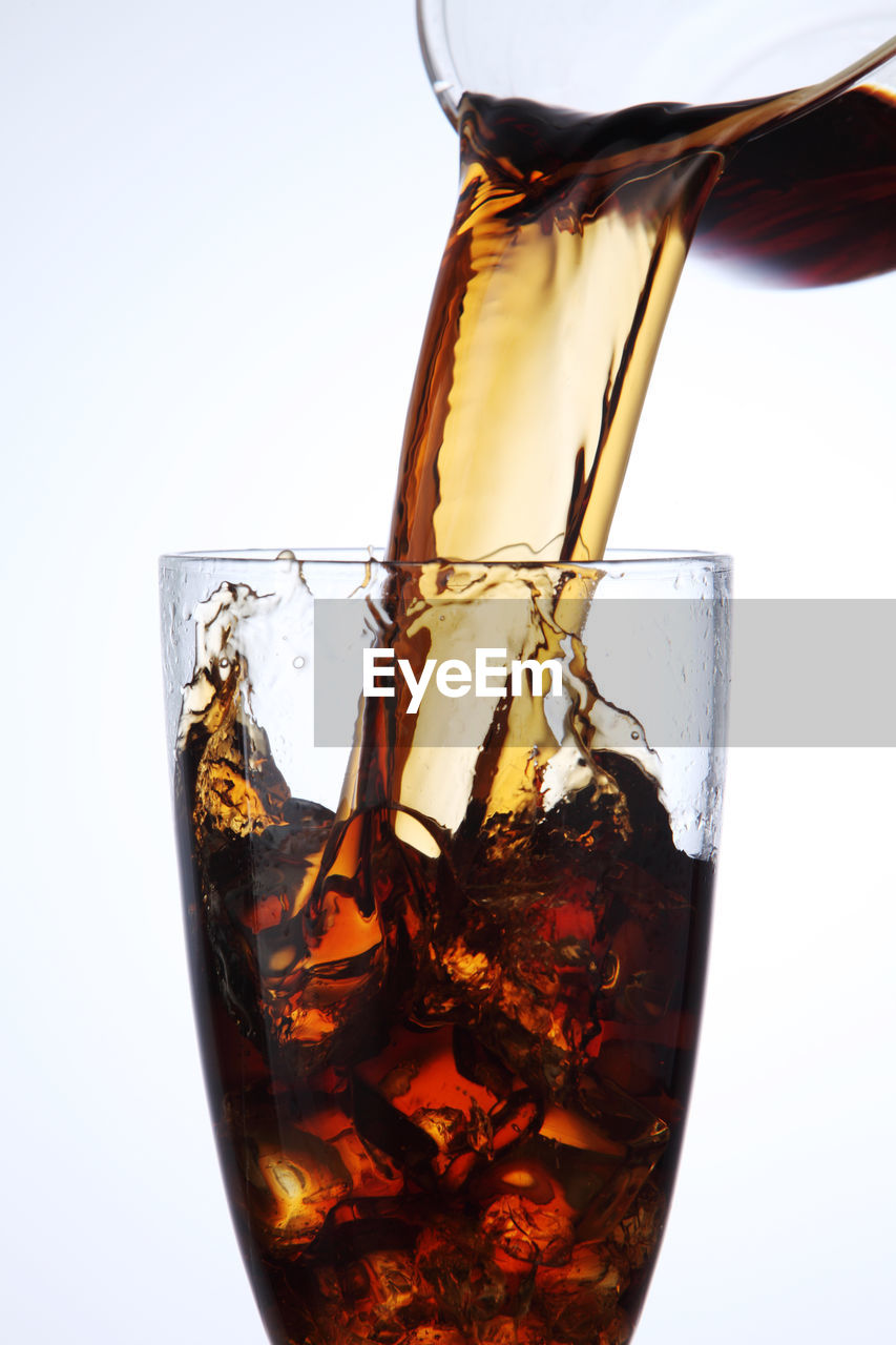 Close-up of jug pouring drink in glass against white background