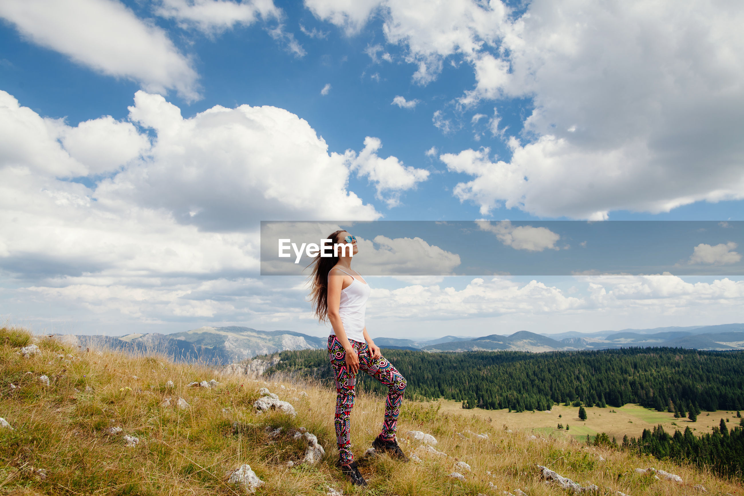 Full length of woman standing on field against cloudy sky