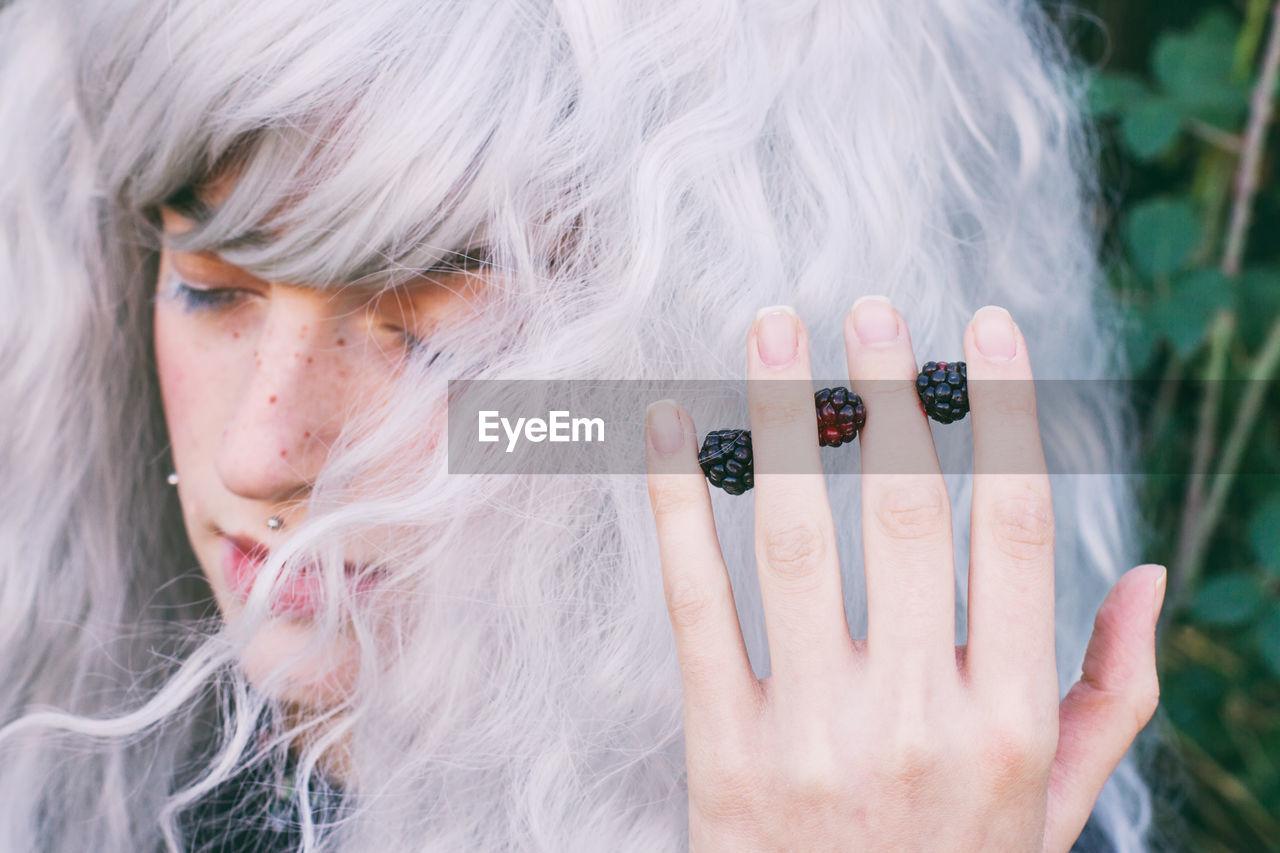 Close-Up Of Female Model Holding Blackberries