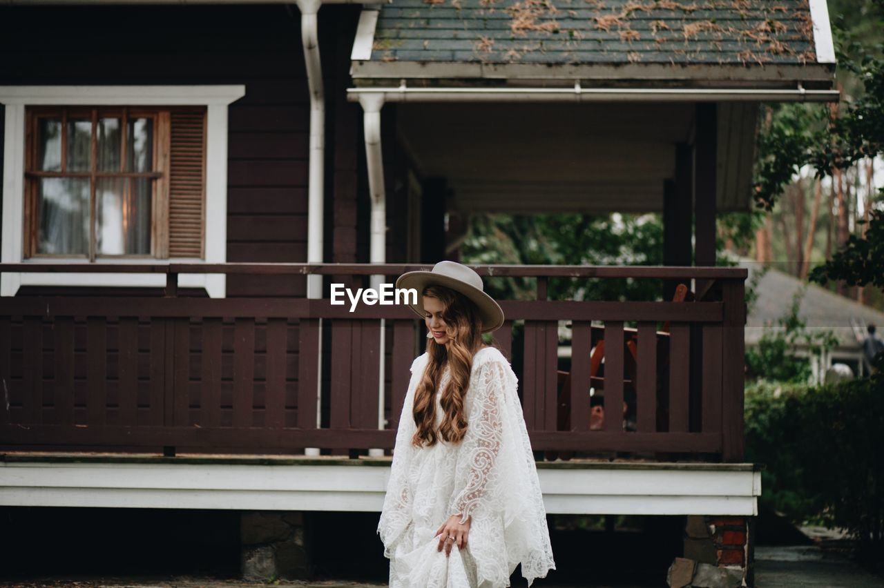 Bride wearing hat while standing against house
