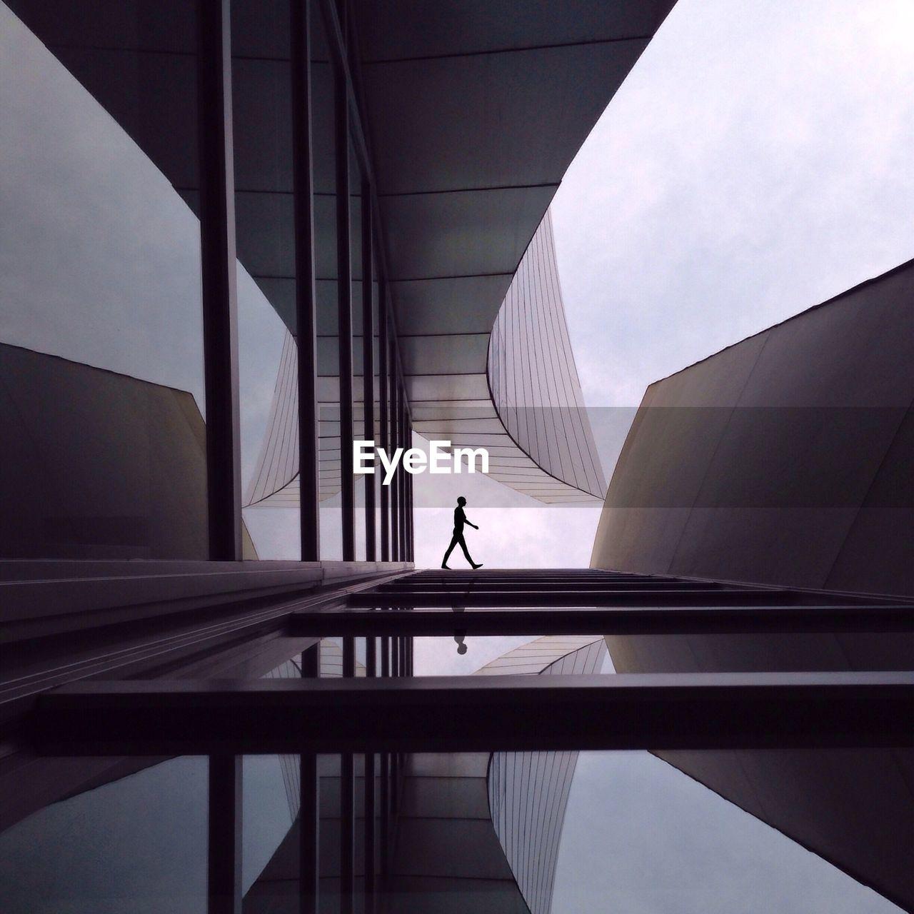 Silhouette Person Walking Outside Modern Building