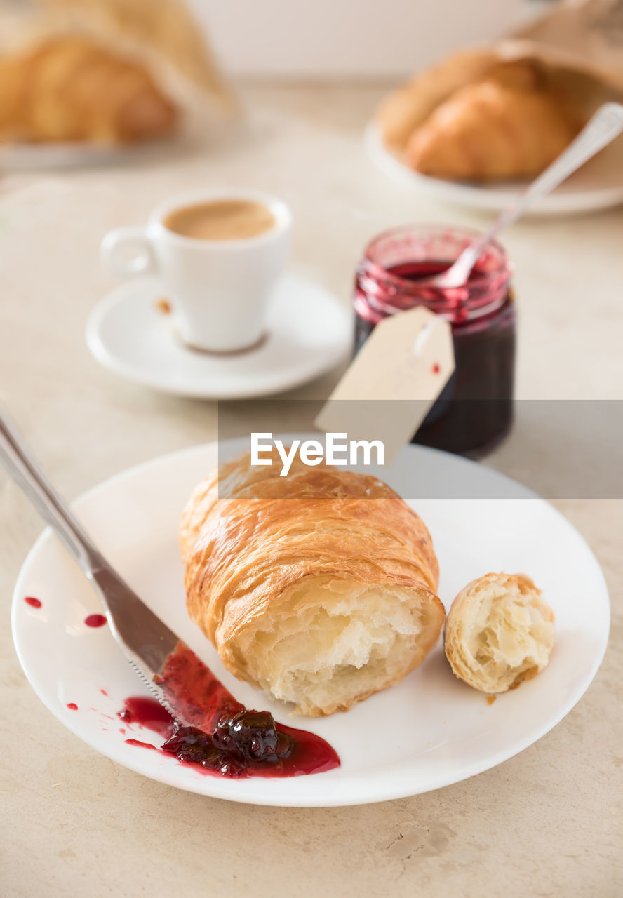 food and drink, plate, table, food, cup, croissant, drink, coffee cup, refreshment, mug, coffee, still life, baked, coffee - drink, french food, ready-to-eat, indoors, breakfast, sweet food, serving size, meal, no people, baked pastry item, strawberry jam, temptation, crockery