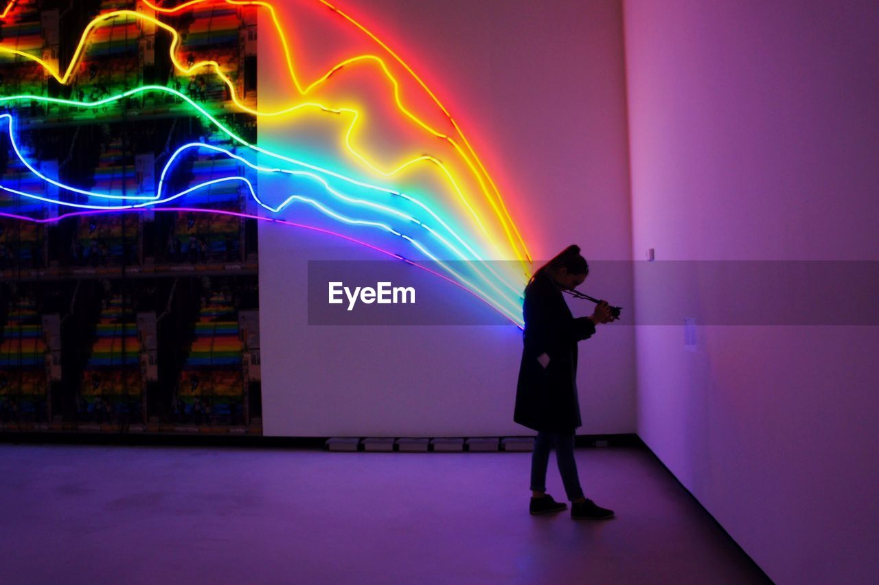 Full Length Of Woman Photographing Against Multi Colored Light Art In Maxxi National Museum
