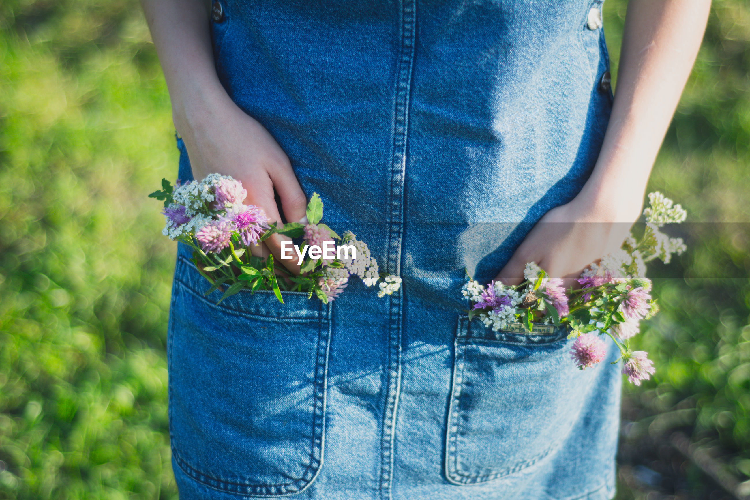 Midsection of woman with flowers in pockets