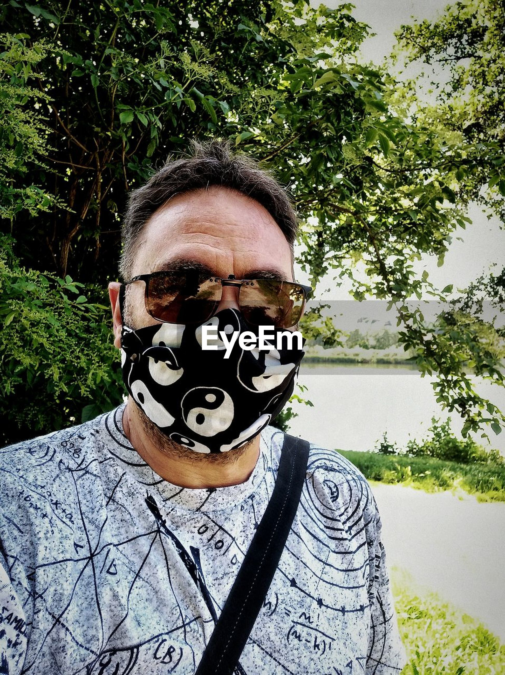 one person, portrait, looking at camera, clothing, headshot, plant, tree, front view, disguise, adult, men, mask, day, mask - disguise, leisure activity, glasses, young adult, nature, outdoors, lifestyles, costume, human face, obscured face, person, art, standing, casual clothing