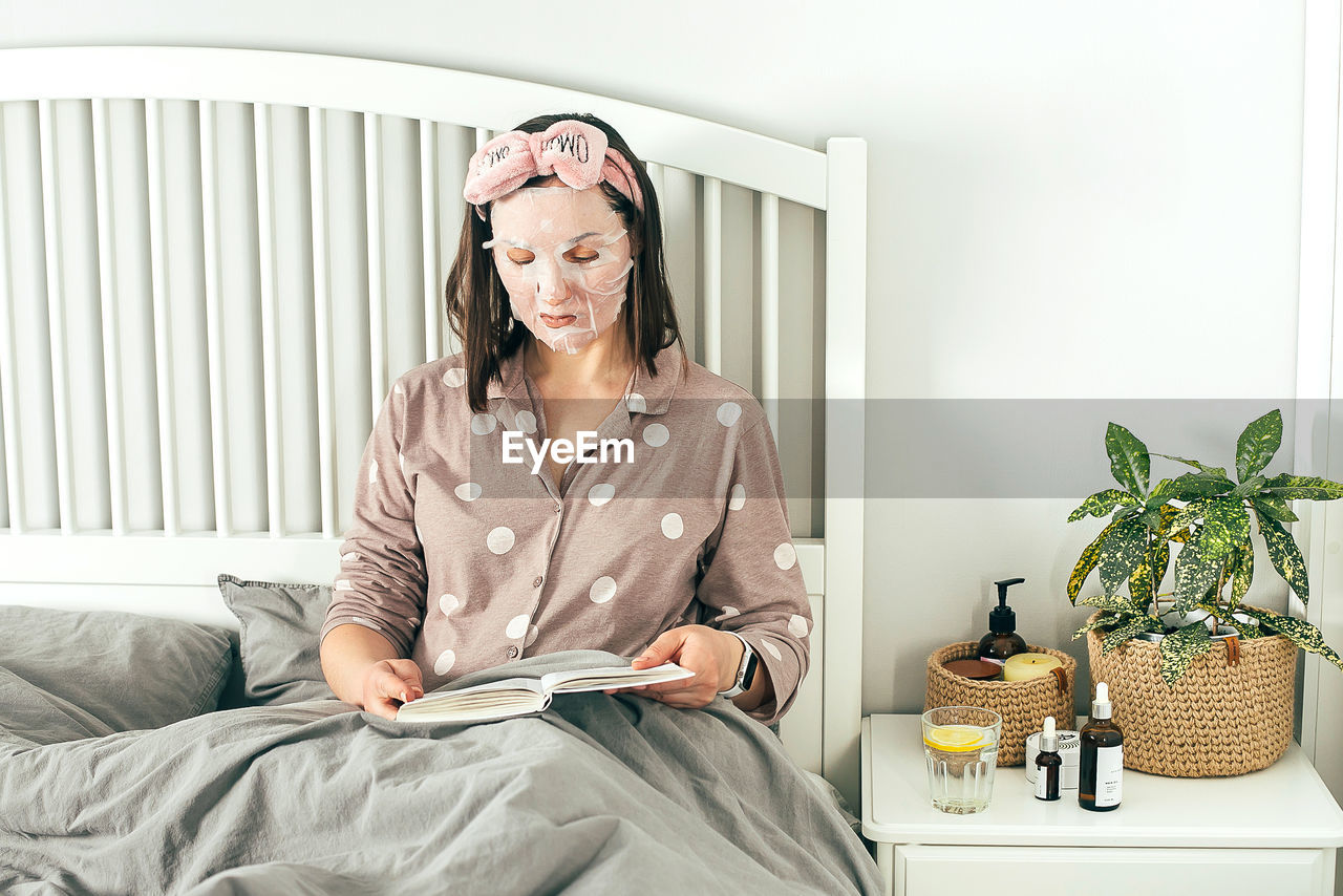 Woman with face mask reading book while while sitting on bed at home