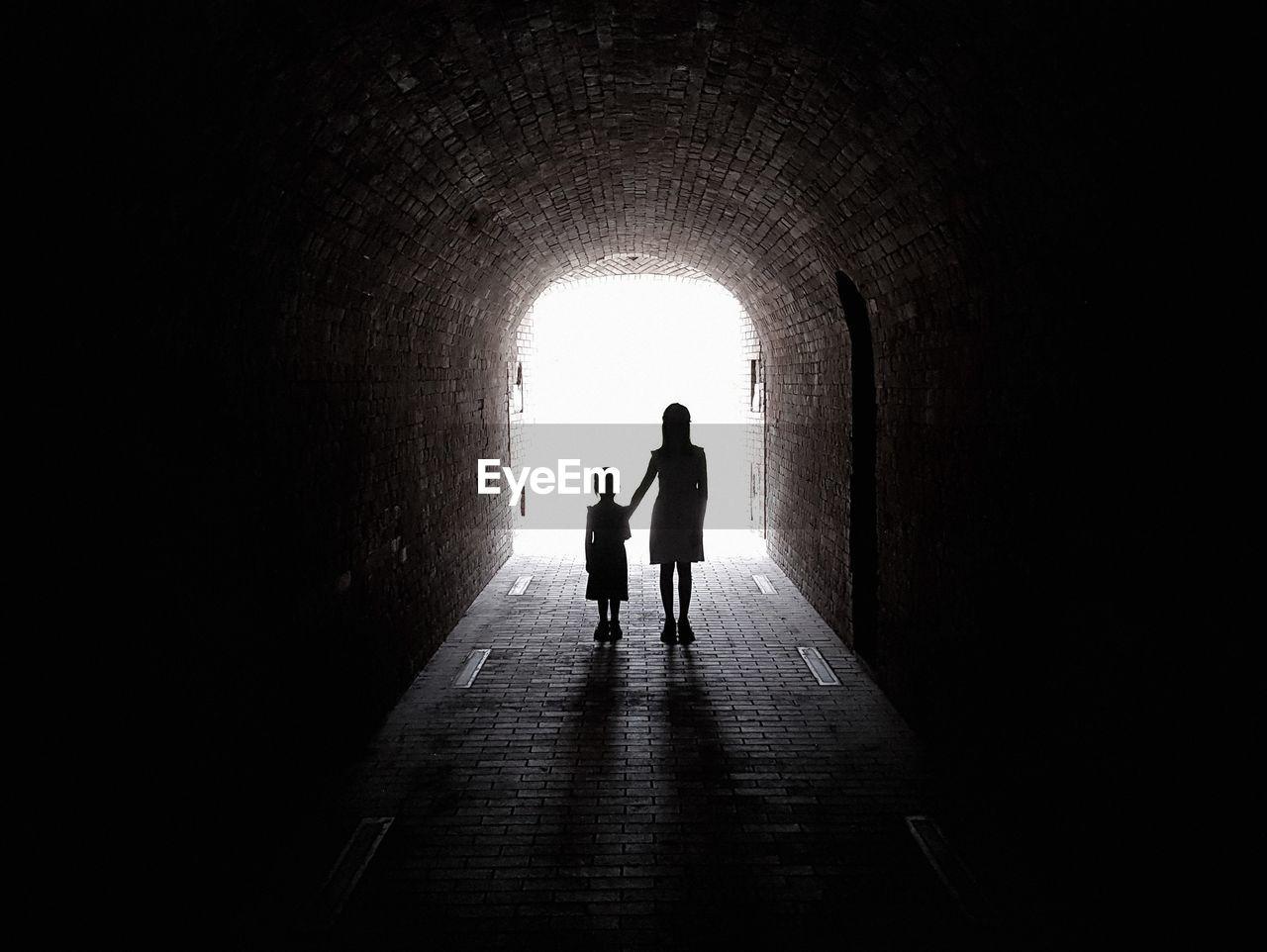 Silhouette Siblings Standing In Archway