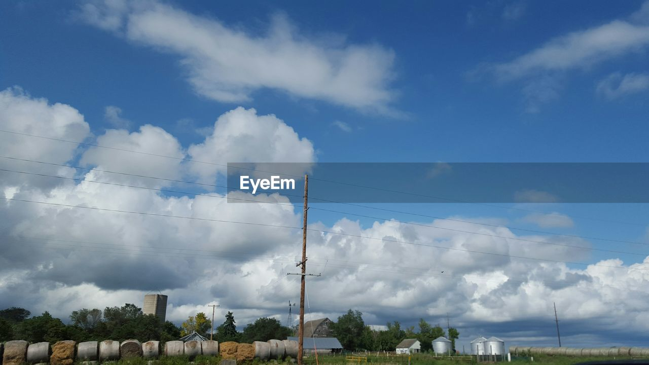 Electricity pylon on field against cloudy sky