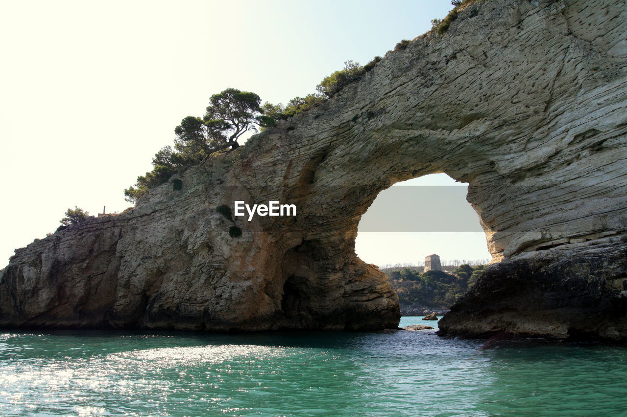 sky, rock, rock - object, arch, rock formation, solid, water, sea, natural arch, nature, day, waterfront, beauty in nature, architecture, scenics - nature, clear sky, tranquility, land, outdoors, no people