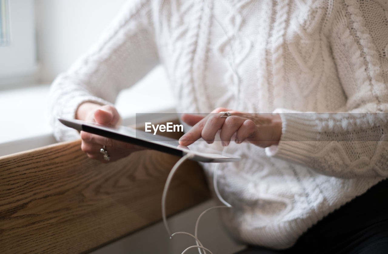 Midsection Of Woman Using Digital Tablet At Home