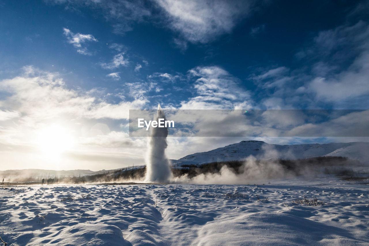Geyser By Snow Field Against Sky