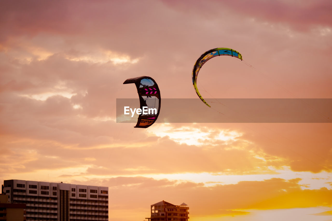 sunset, extreme sports, adventure, sky, mid-air, leisure activity, cloud - sky, sport, nature, exhilaration, parachute, low angle view, real people, beauty in nature, outdoors, flying, paragliding, scenics, one person, multi colored, day