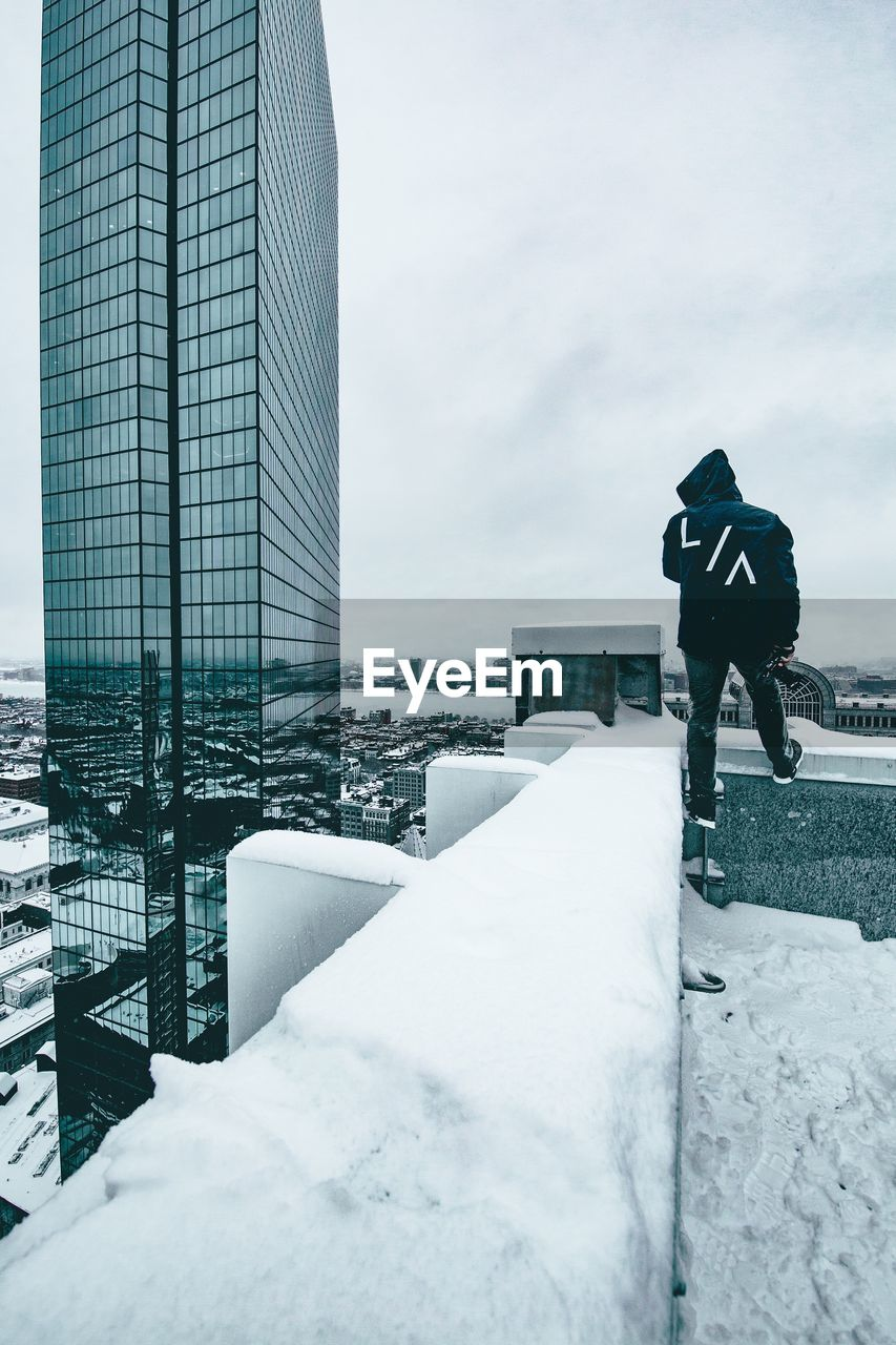 MAN STANDING ON SNOW COVERED CITY