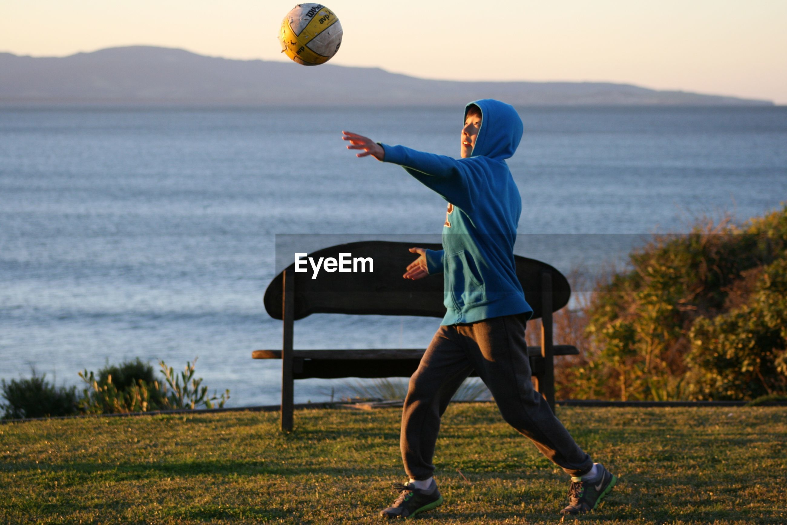 Side view of boy playing soccer on field with lake in background