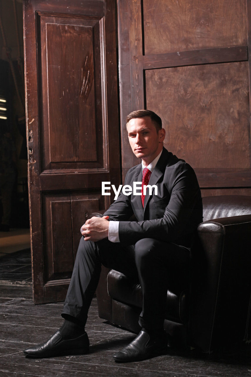 Portrait of businessman sitting on sofa indoors