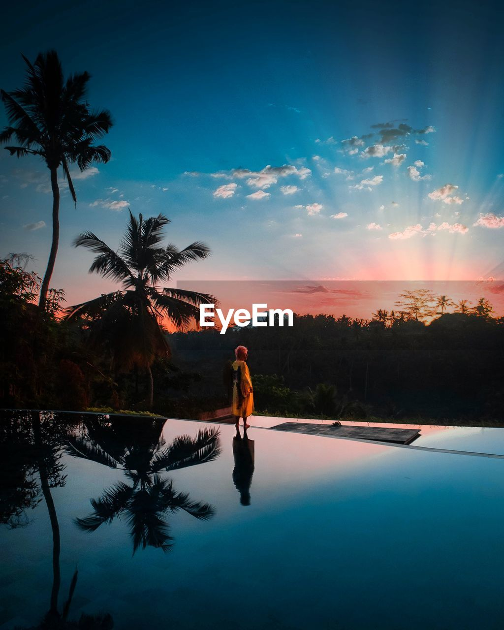 tree, sky, water, tropical climate, palm tree, one person, plant, swimming pool, real people, beauty in nature, scenics - nature, nature, sunset, cloud - sky, pool, lifestyles, reflection, leisure activity, infinity pool, outdoors