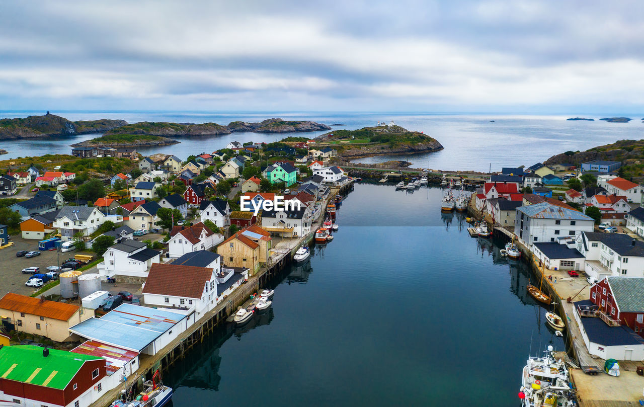 HIGH ANGLE VIEW OF TOWNSCAPE AND SEA AGAINST SKY