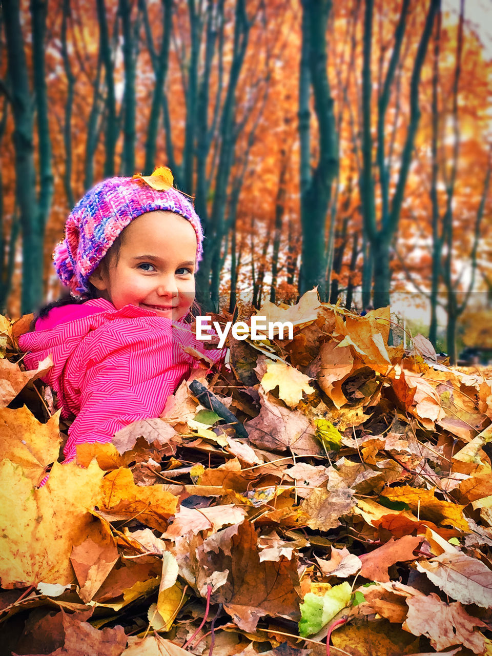 GIRL IN AUTUMN LEAVES ON TREE