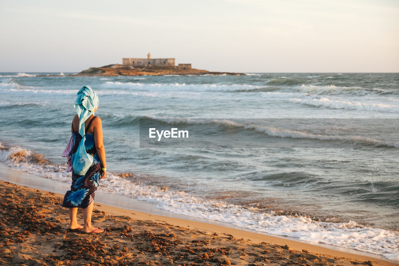 sea, real people, beach, full length, wave, water, one person, nature, standing, horizon over water, walking, beauty in nature, rear view, leisure activity, scenics, sky, outdoors, lifestyles, day, vacations, sunset, adult, people