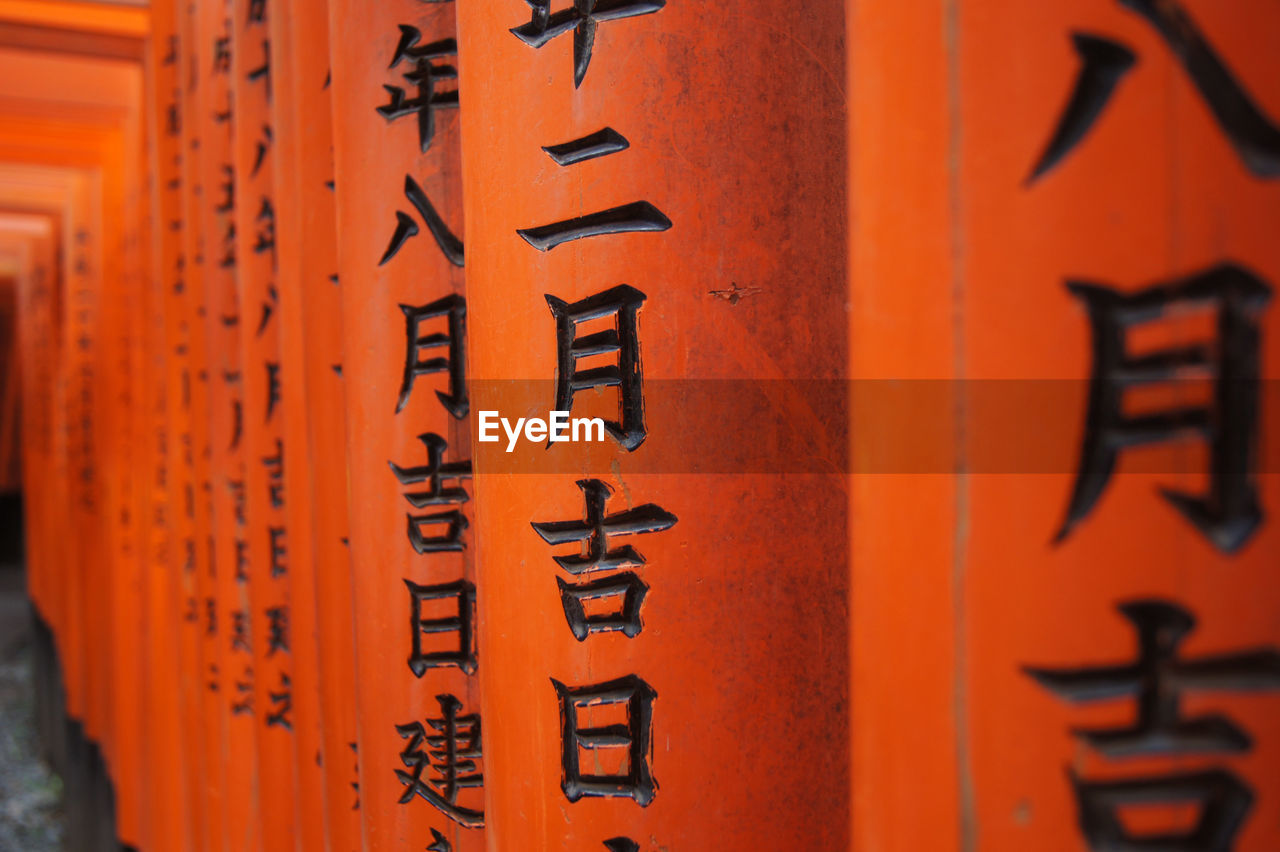 text, script, non-western script, communication, belief, religion, no people, spirituality, place of worship, close-up, orange color, selective focus, red, architecture, focus on foreground, day, message, shrine