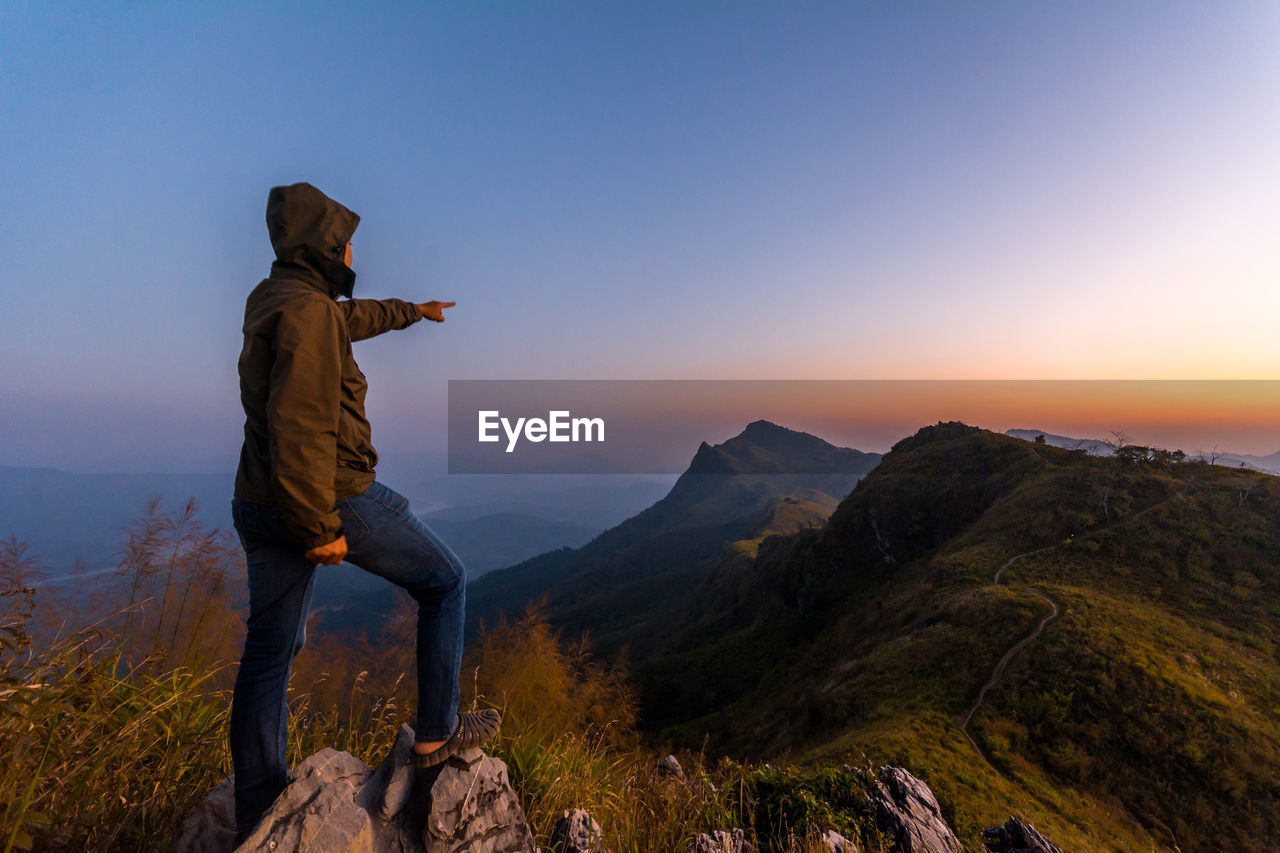 real people, mountain, full length, one person, nature, beauty in nature, leisure activity, sunset, lifestyles, scenics, outdoors, mountain range, casual clothing, standing, adventure, sky, rear view, clear sky, tranquility, hiking, men, women, landscape, day, young adult, people