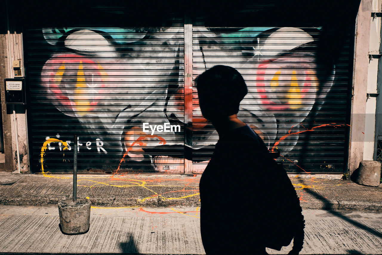 REAR VIEW OF WOMAN WALKING ON STREET AGAINST GRAFFITI
