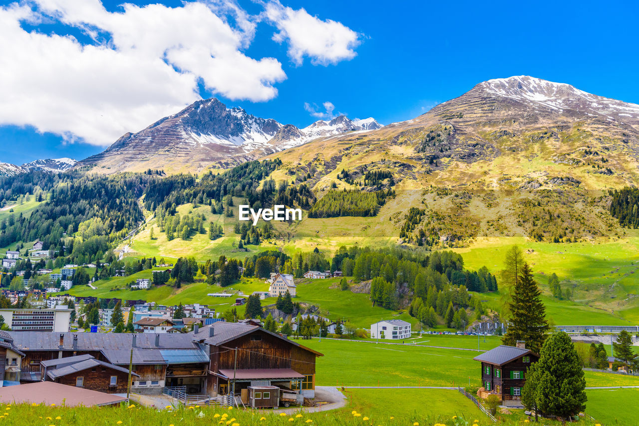mountain, sky, scenics - nature, architecture, beauty in nature, built structure, cloud - sky, plant, landscape, building exterior, tree, nature, building, environment, green color, no people, day, mountain range, tranquil scene, grass, outdoors, snowcapped mountain, mountain peak