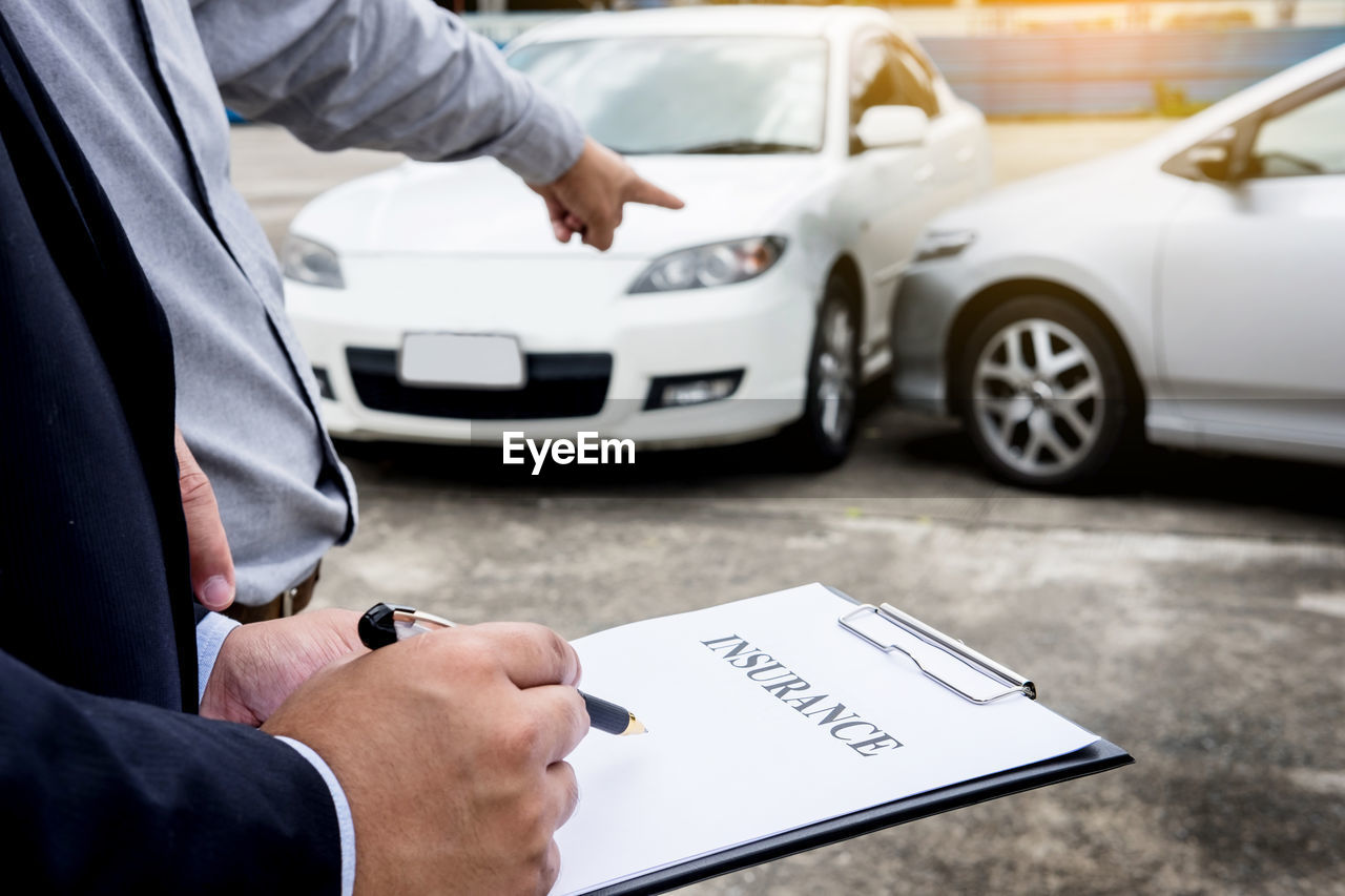 Cropped hand of man with customer writing on insurance paper
