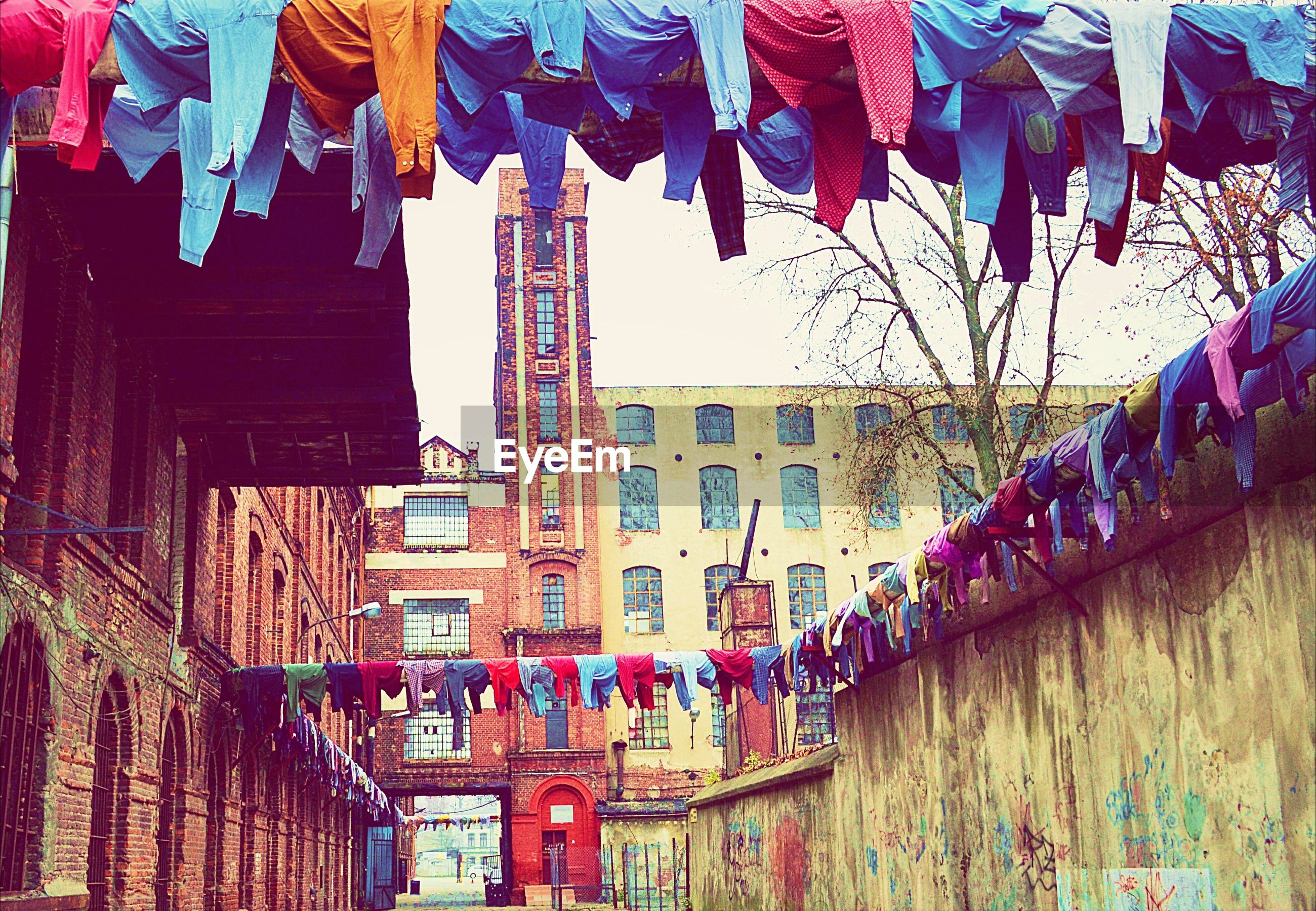 Low angle view of clothesline at buildings against clear sky