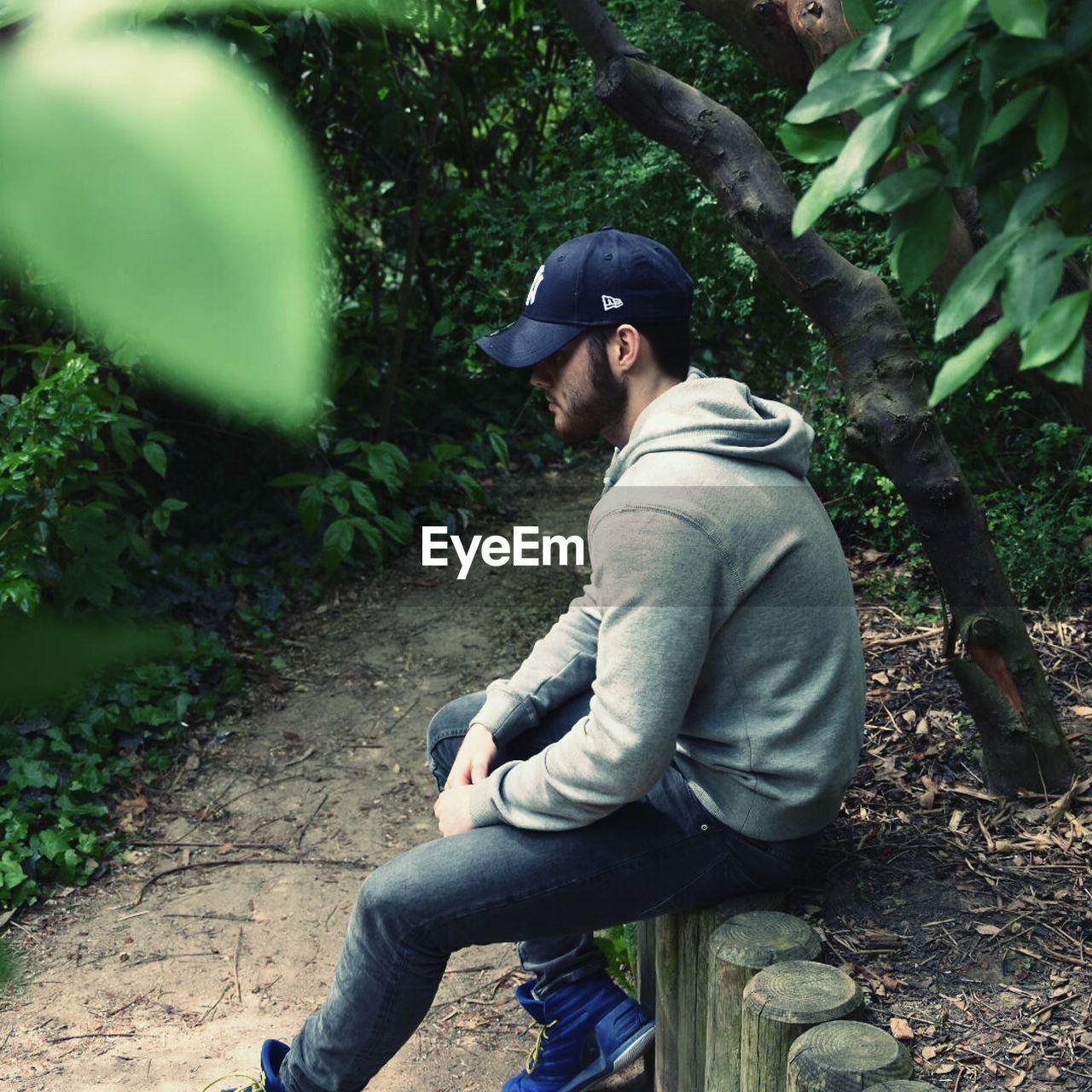FULL LENGTH OF MAN SITTING ON TREE