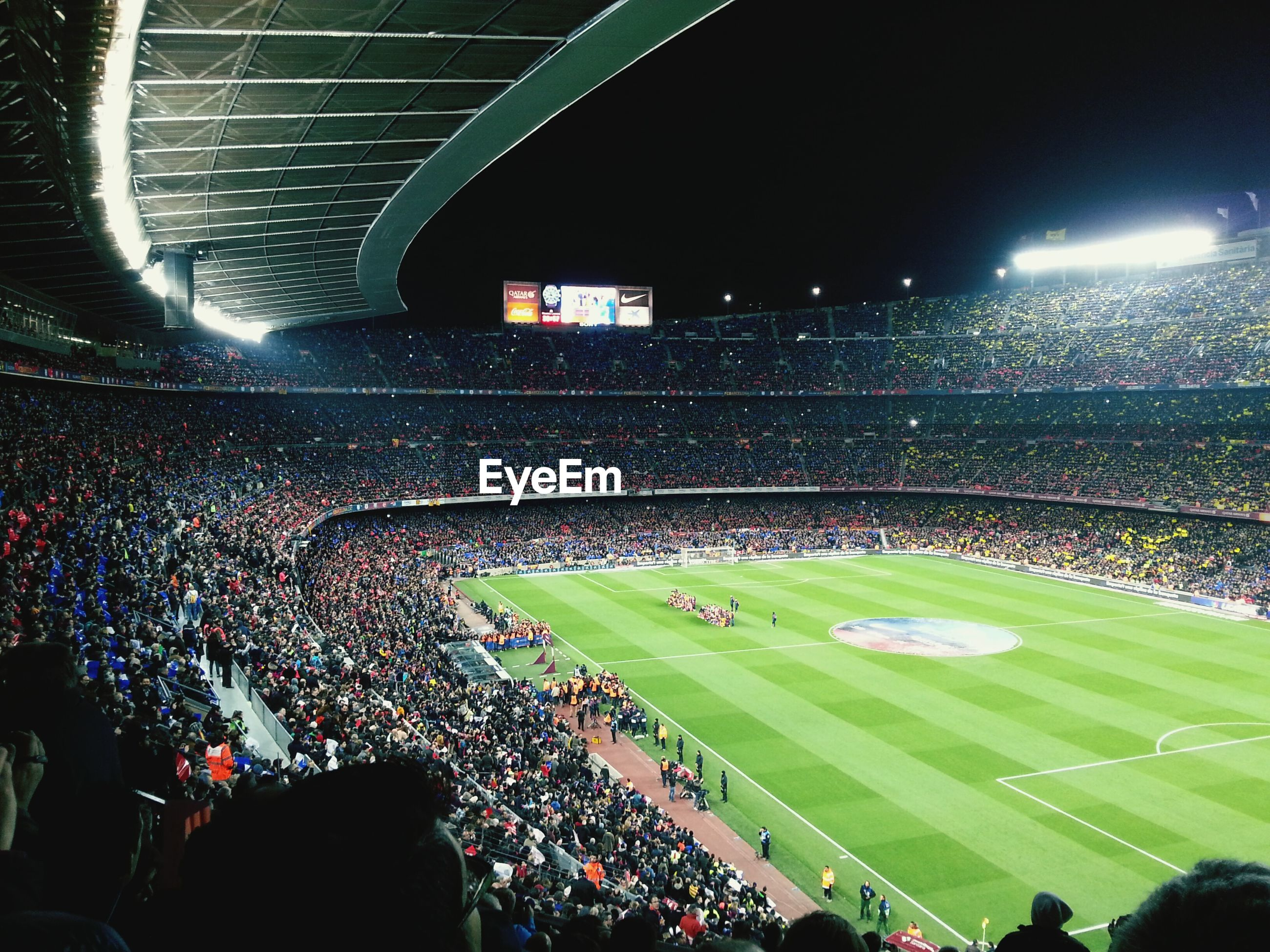 large group of people, illuminated, crowd, high angle view, night, green color, built structure, architecture, stadium, sport, arts culture and entertainment, leisure activity, lighting equipment, travel, outdoors, men, city life, travel destinations, grass