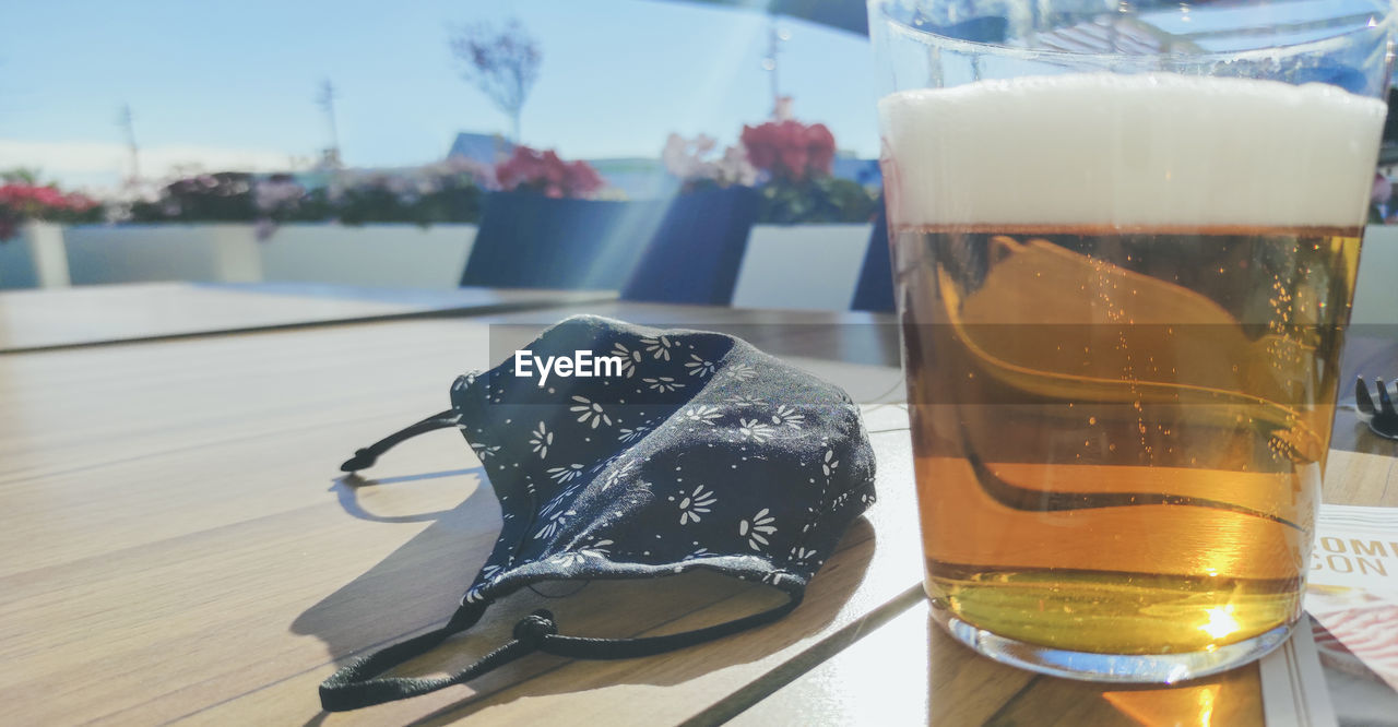 CLOSE-UP OF BEER GLASS ON TABLE AGAINST BLURRED BACKGROUND