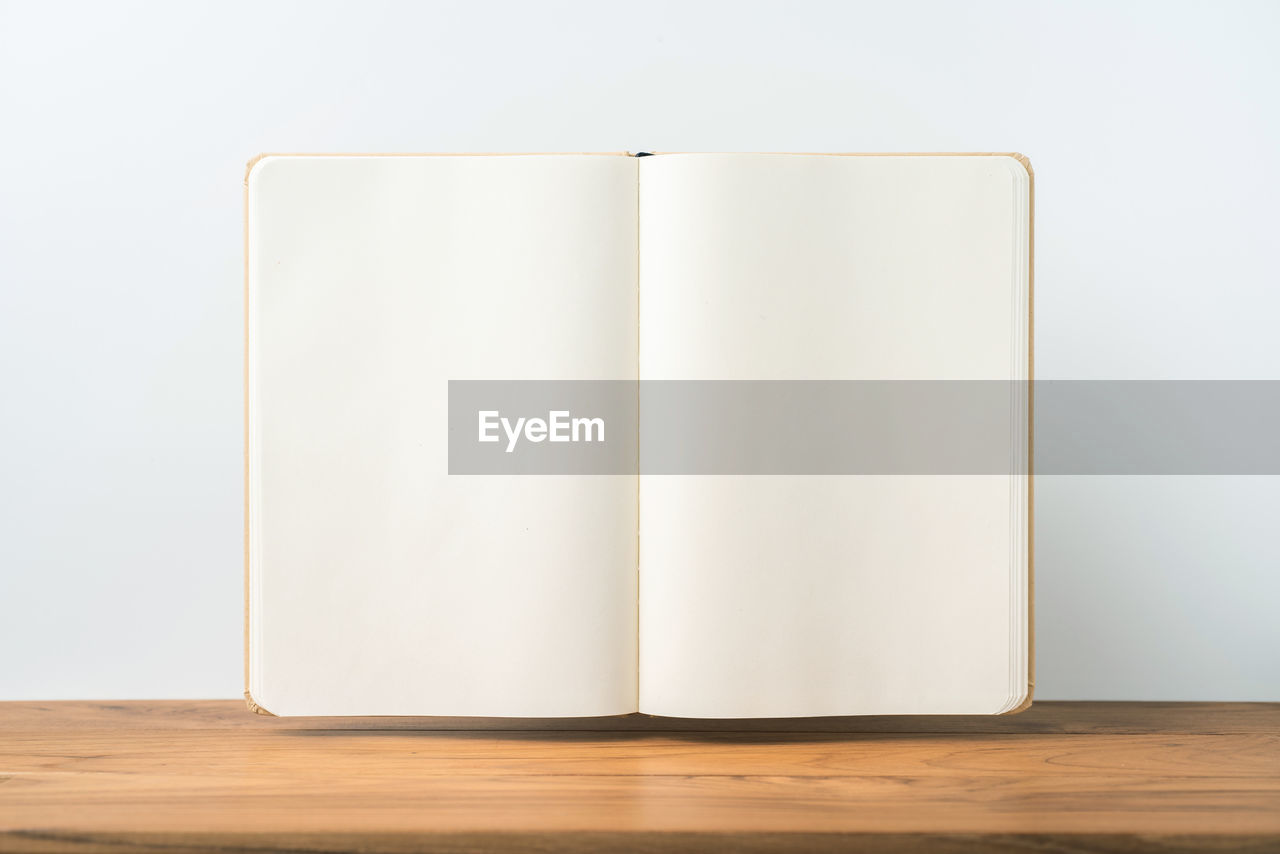 copy space, blank, publication, white color, indoors, book, still life, paper, wood - material, table, no people, page, white background, education, studio shot, open, wall - building feature, close-up, empty, technology
