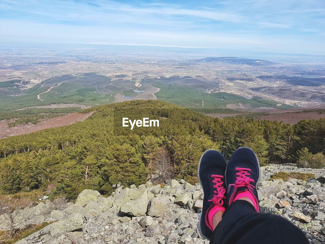Low section of woman wearing shoes resting on mountain