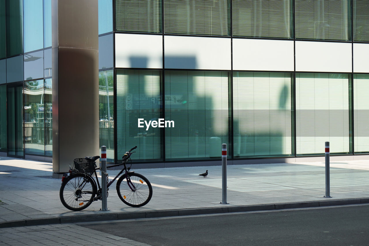 Bicycle Parked By Bollard On Footpath Against Office Building