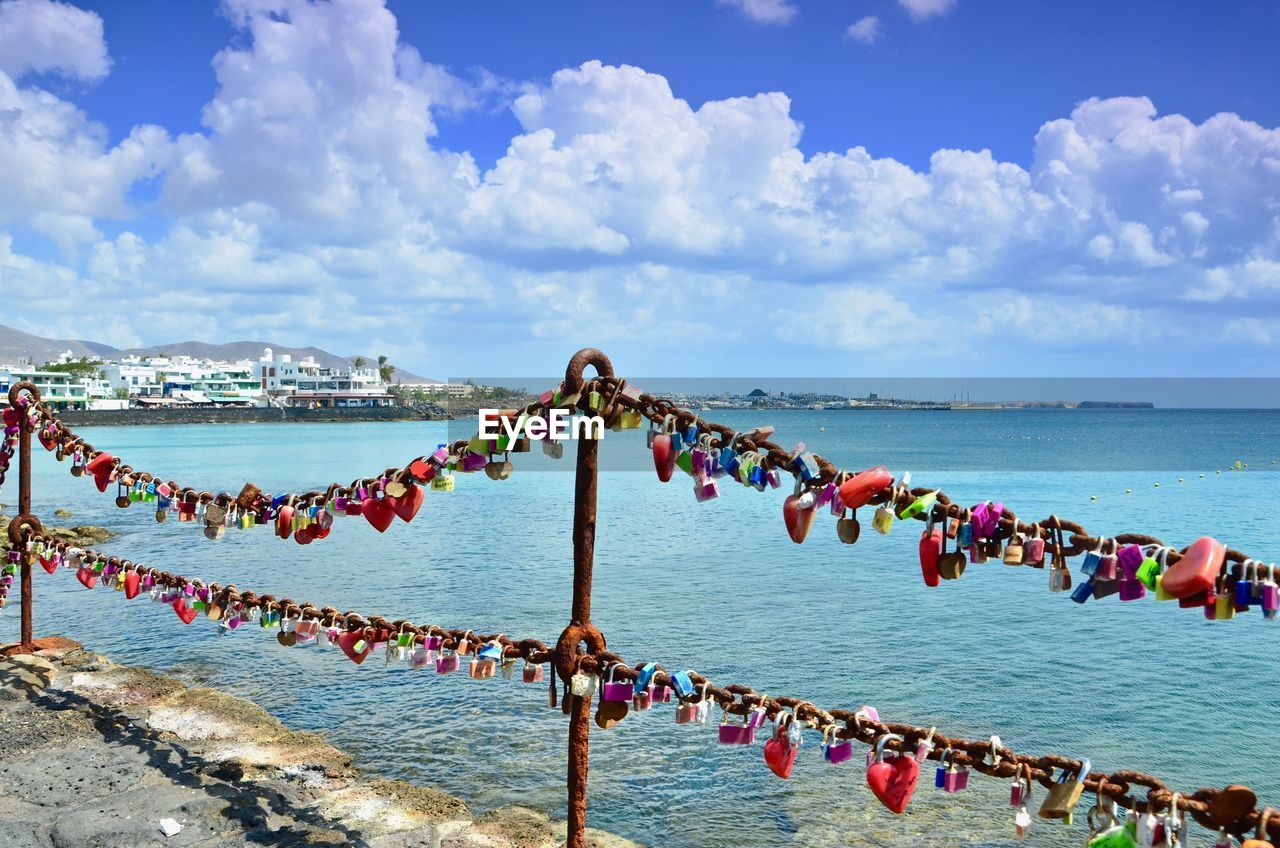 water, cloud - sky, sky, sea, nature, crowd, day, beauty in nature, lock, large group of people, padlock, safety, outdoors, hanging, scenics - nature, protection, land, horizon over water, security