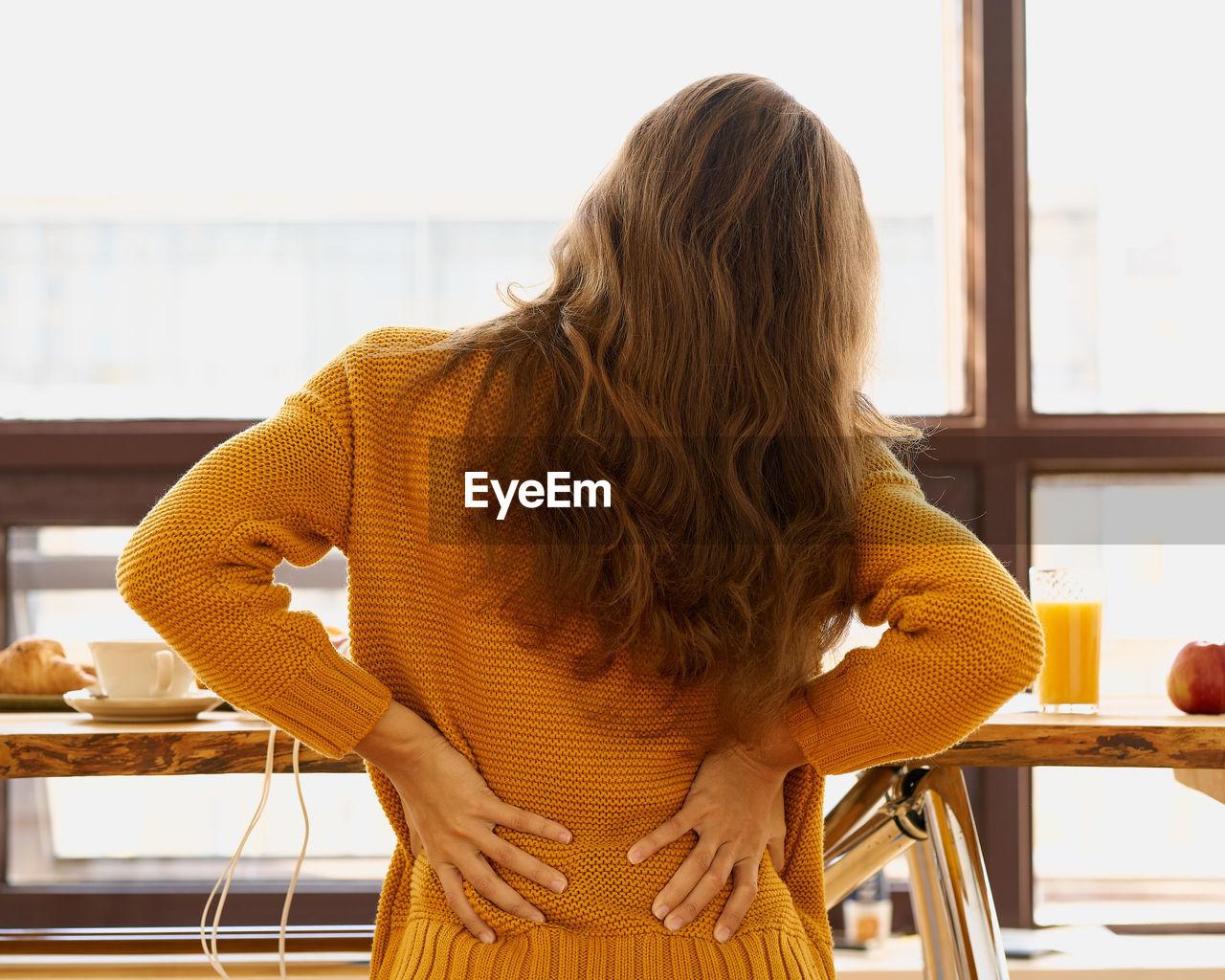Back view of faceless young woman touching back feeling backache, discomfort low lumbar muscular