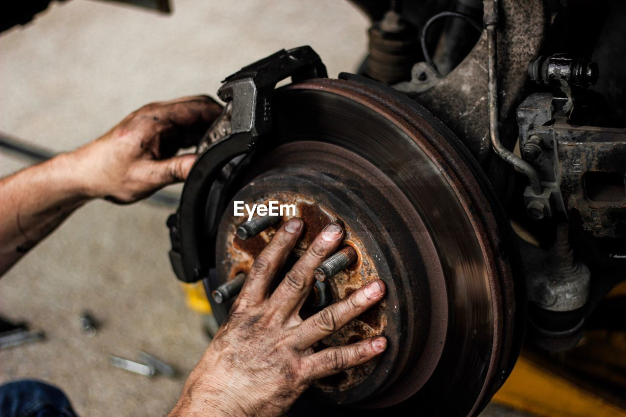 Cropped Hands Of Mechanic Repairing Wheel At Workshop