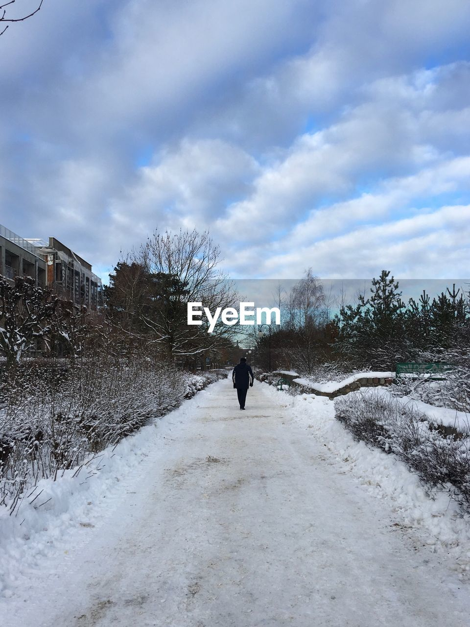 Rear View Of Man Walking On Snow Covered Field Against Cloudy Sky