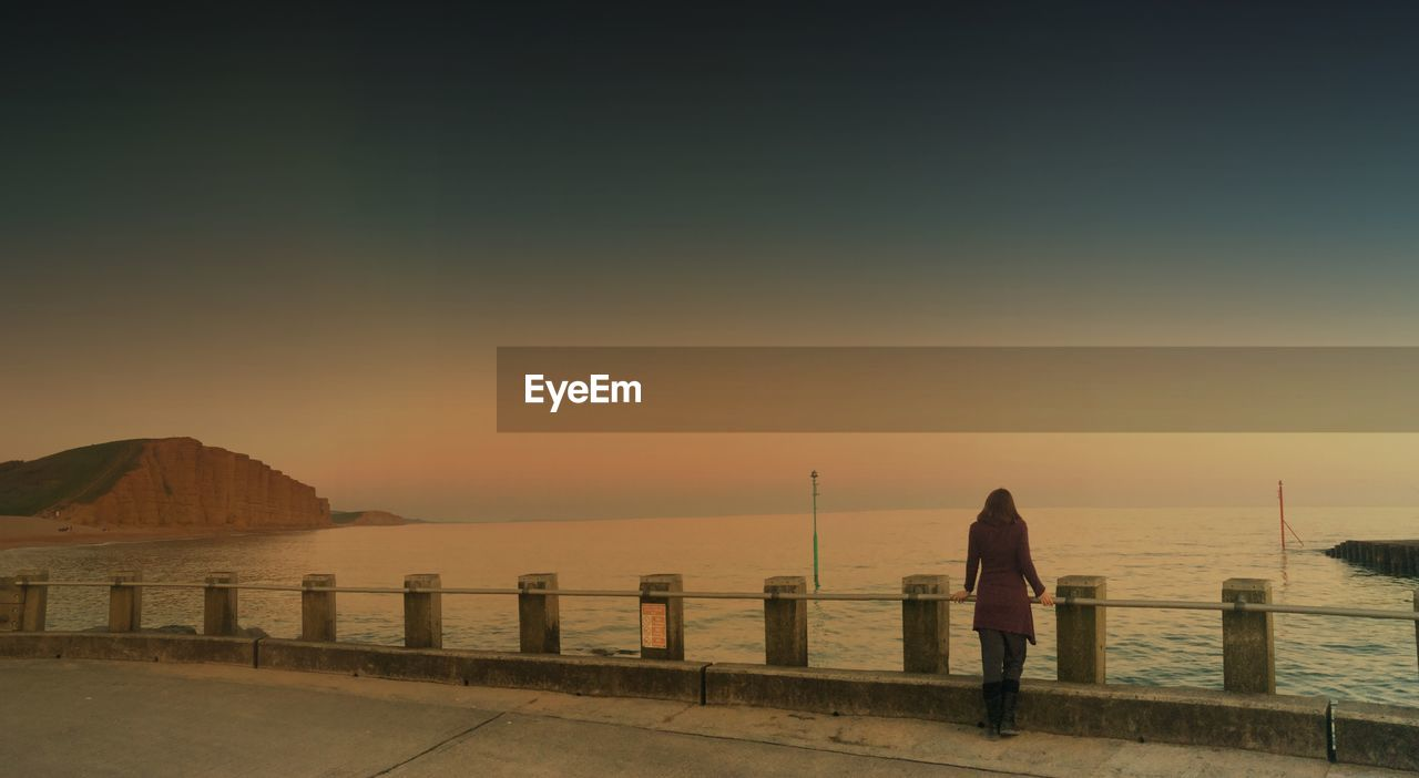 Rear view of woman holding railing in front of sea during sunset against clear sky