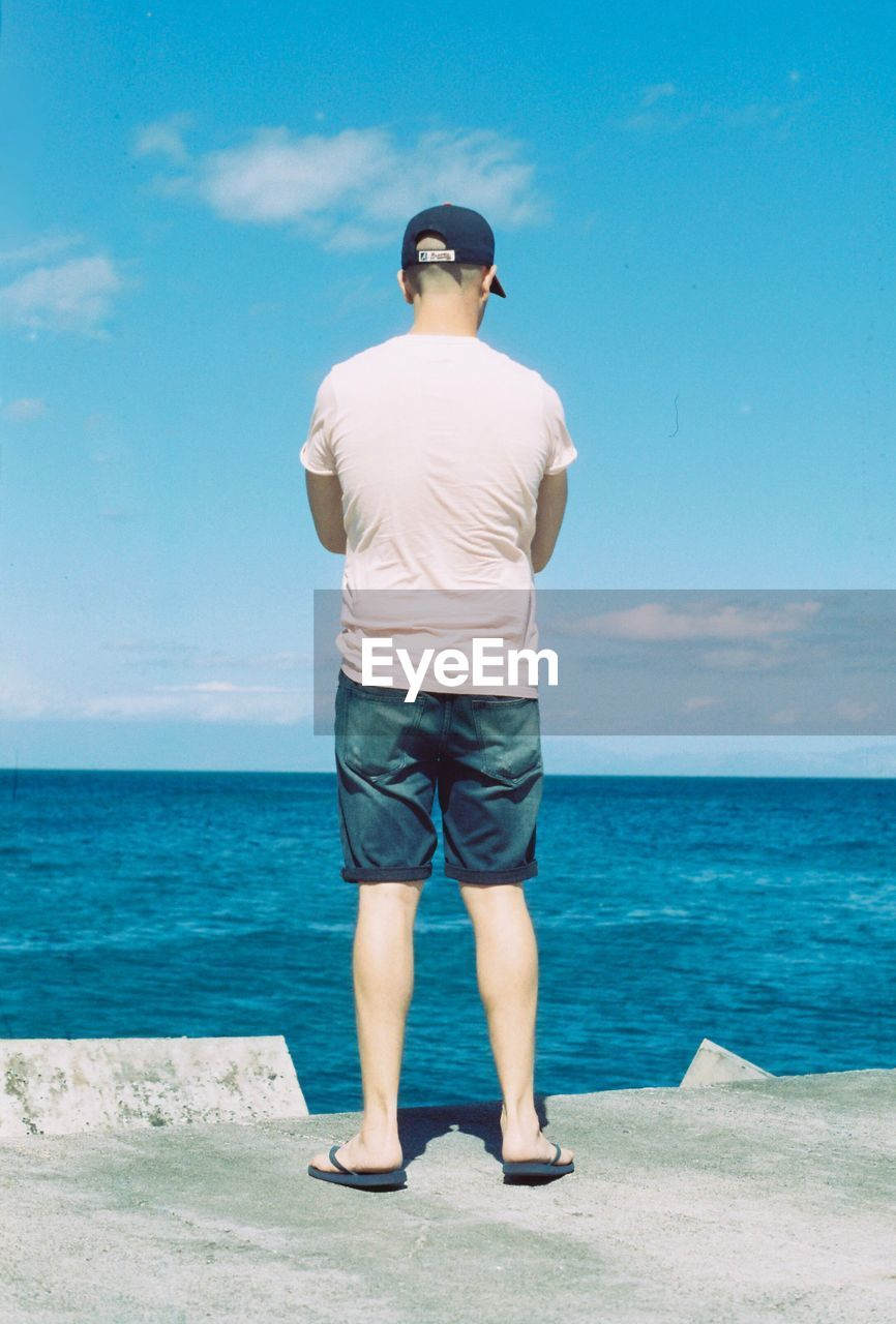 Rear view of man looking at sea against sky during sunny day