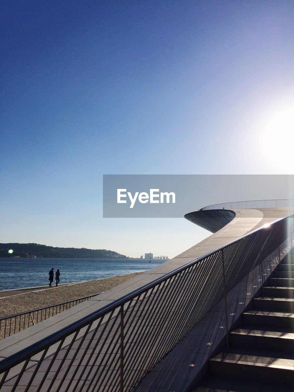 railing, sunlight, built structure, day, clear sky, outdoors, blue, water, architecture, sky, nature, sea, no people