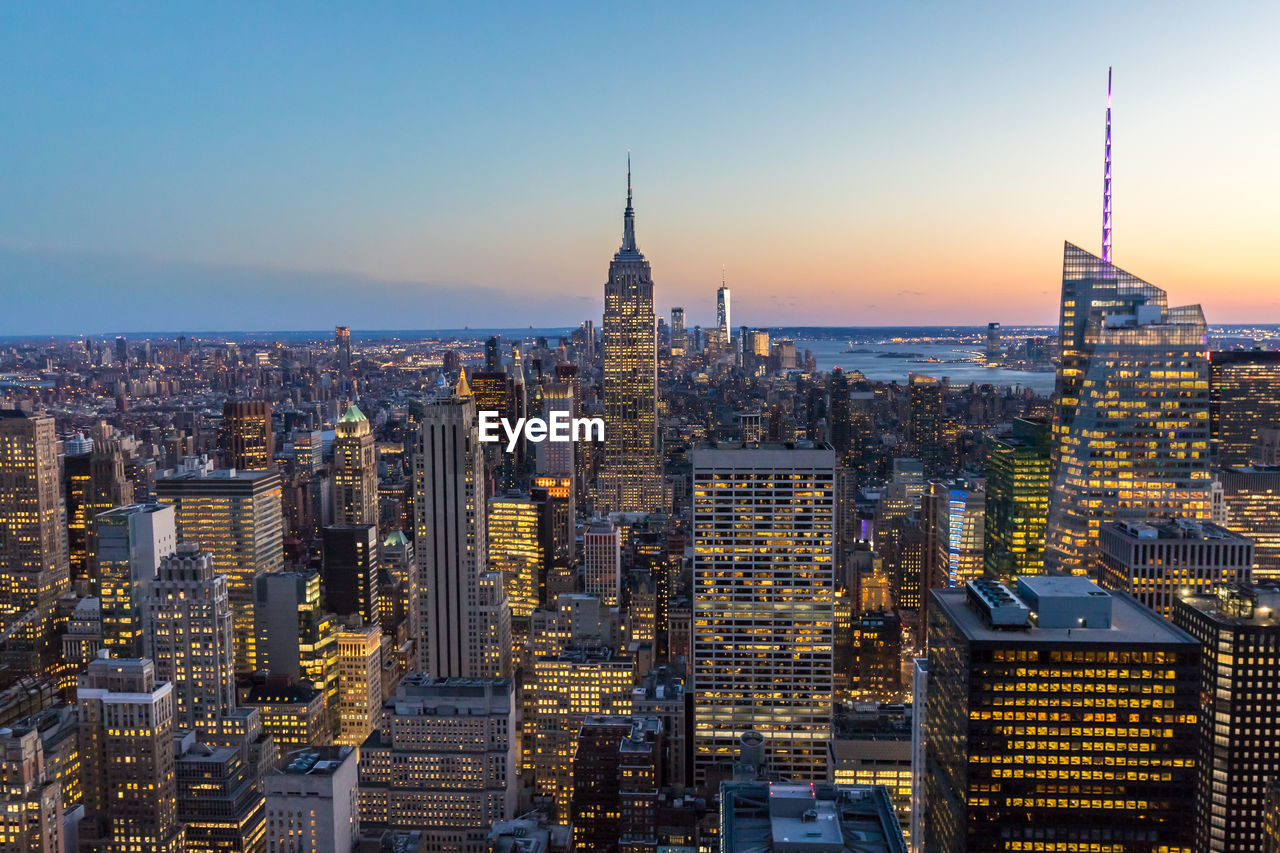 Empire state building amidst cityscape at manhattan during sunset