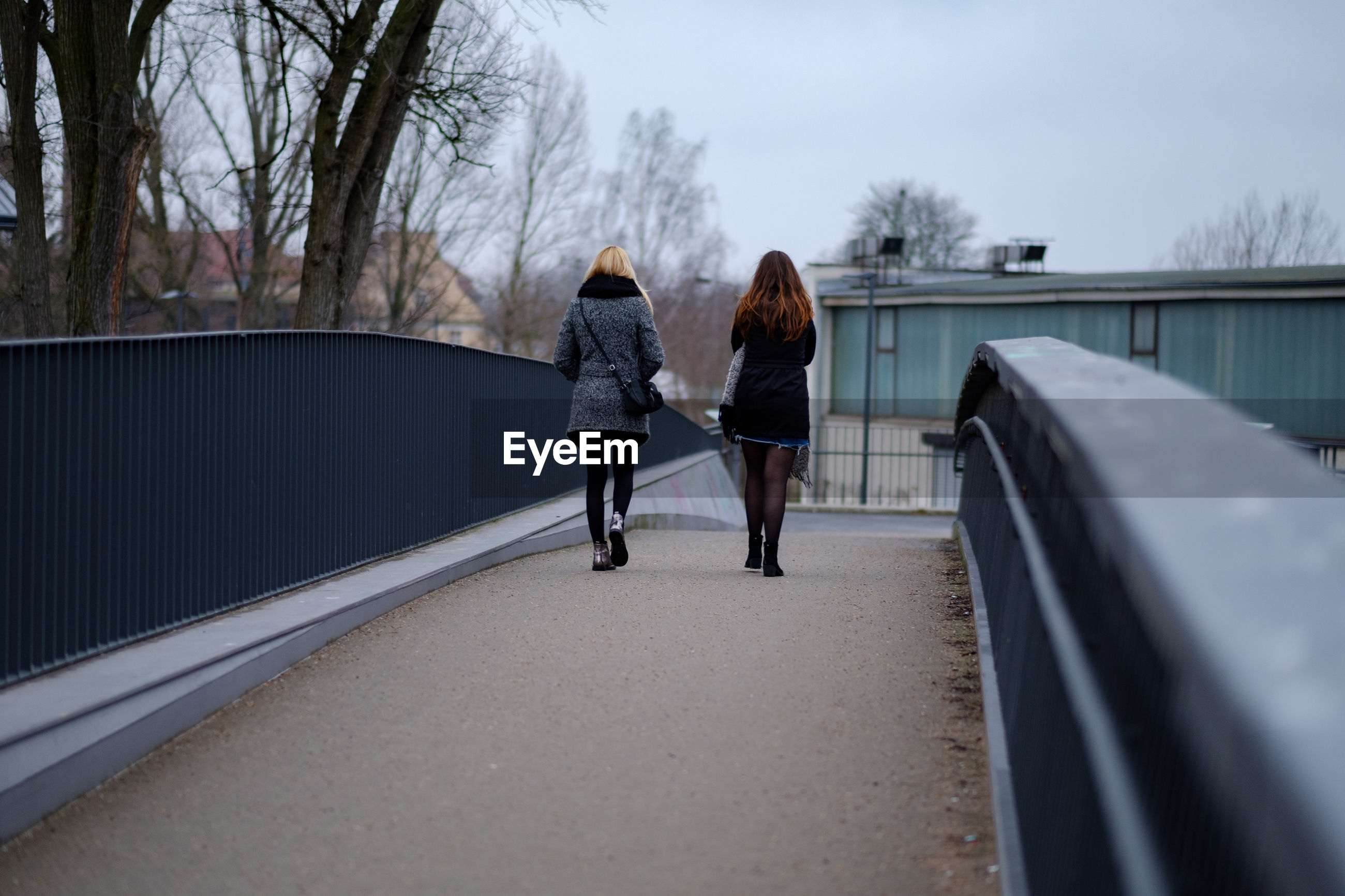 Rear view of women walking on footbridge