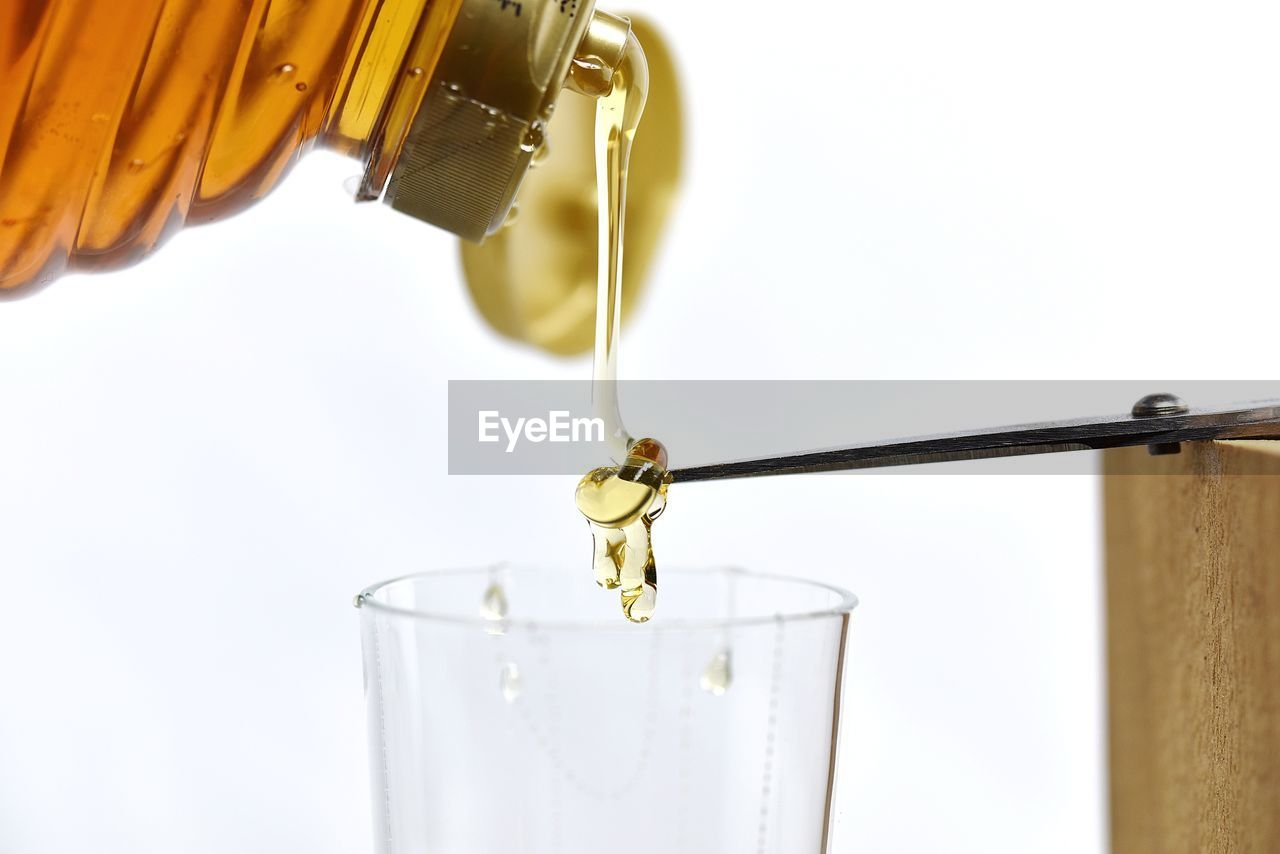 Close-Up Of Honey Pouring In Drinking Glass Against White Background