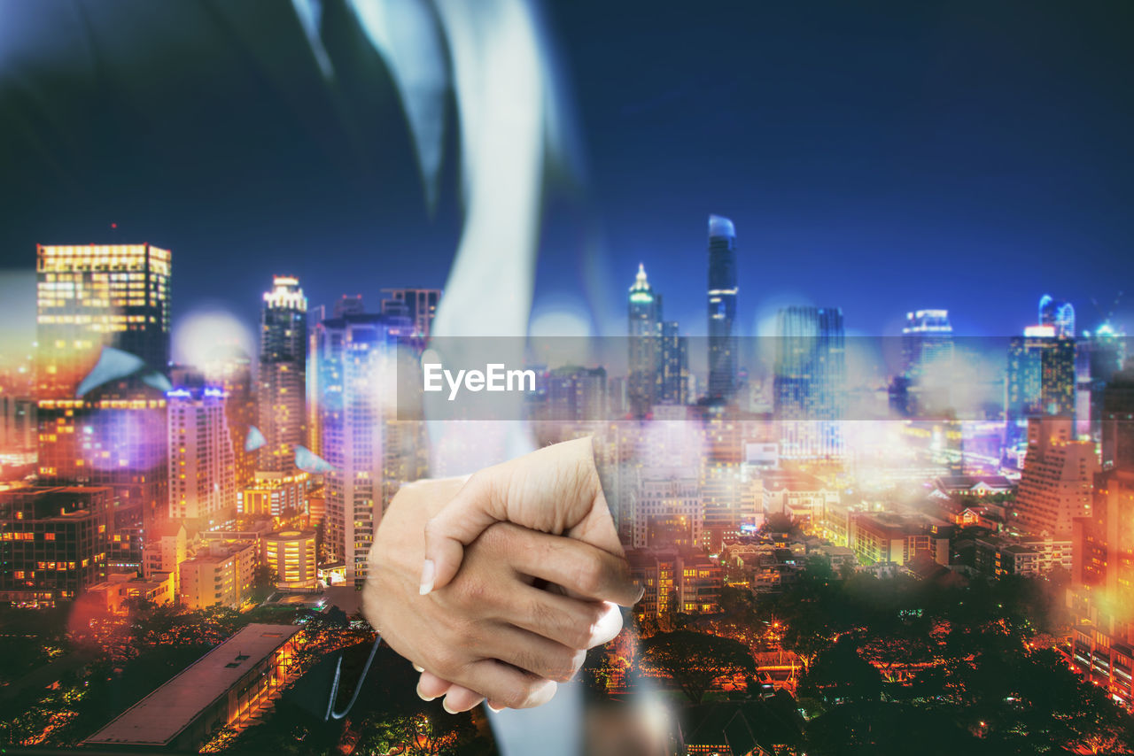 Digital composite of business people shaking hands over cityscape at night